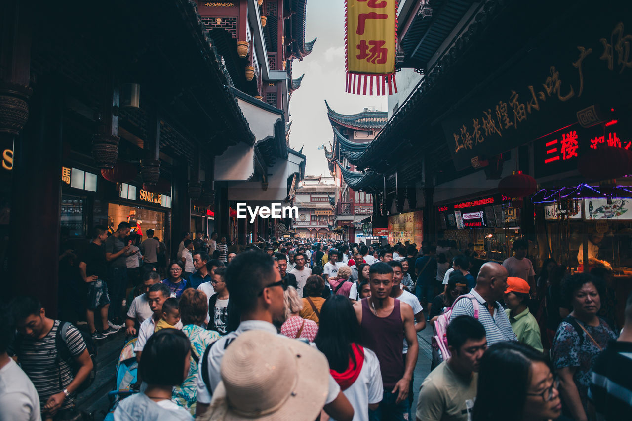 group of people, architecture, city, crowd, large group of people, building exterior, built structure, street, real people, men, women, text, city life, adult, communication, walking, lifestyles, city street, motion, outdoors, street market
