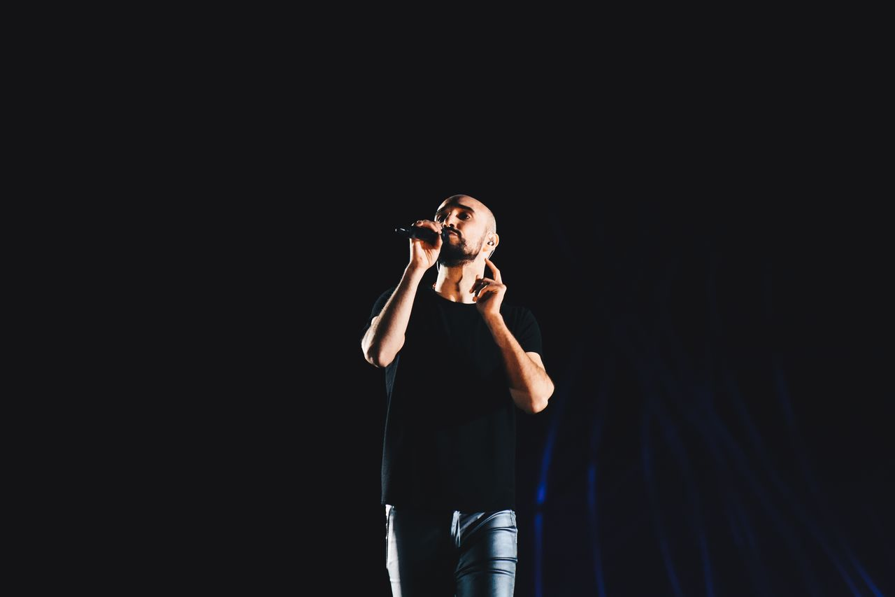 Low Angle View Of Mid Adult Man Singing On Stage At Night