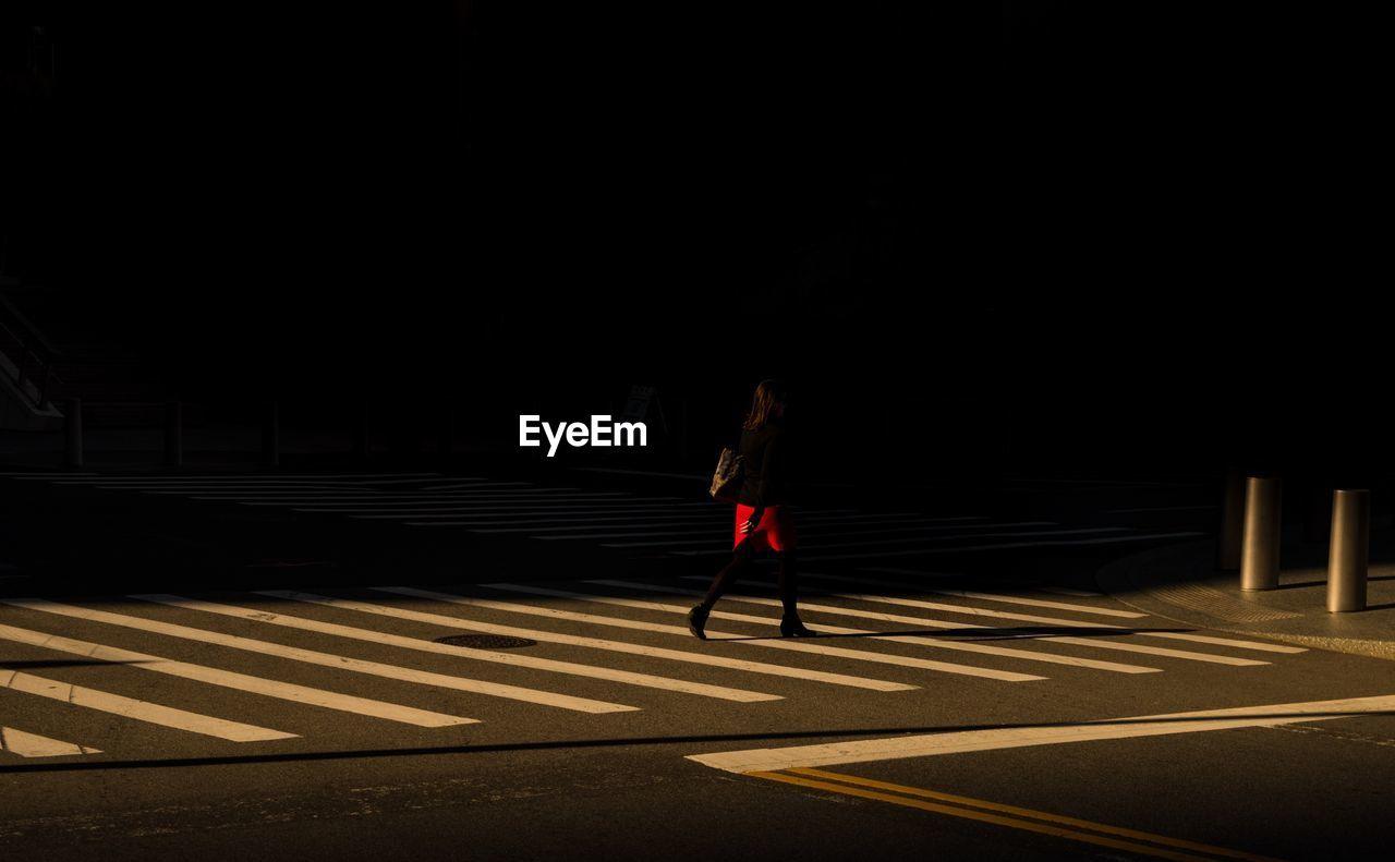 Woman Crossing Road In City