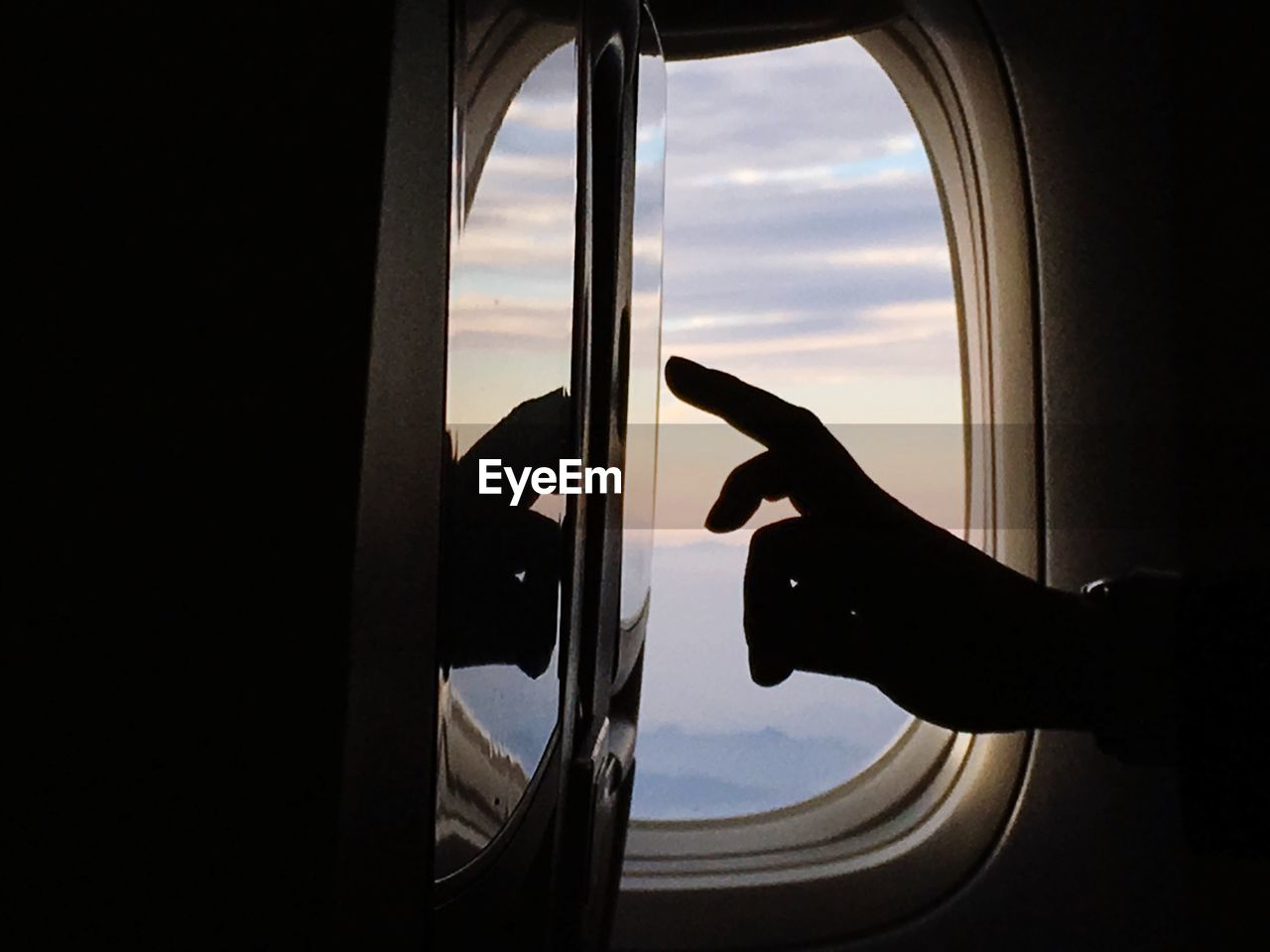 Cropped Image Of Silhouette Hand Touching Device Screen In Airplane