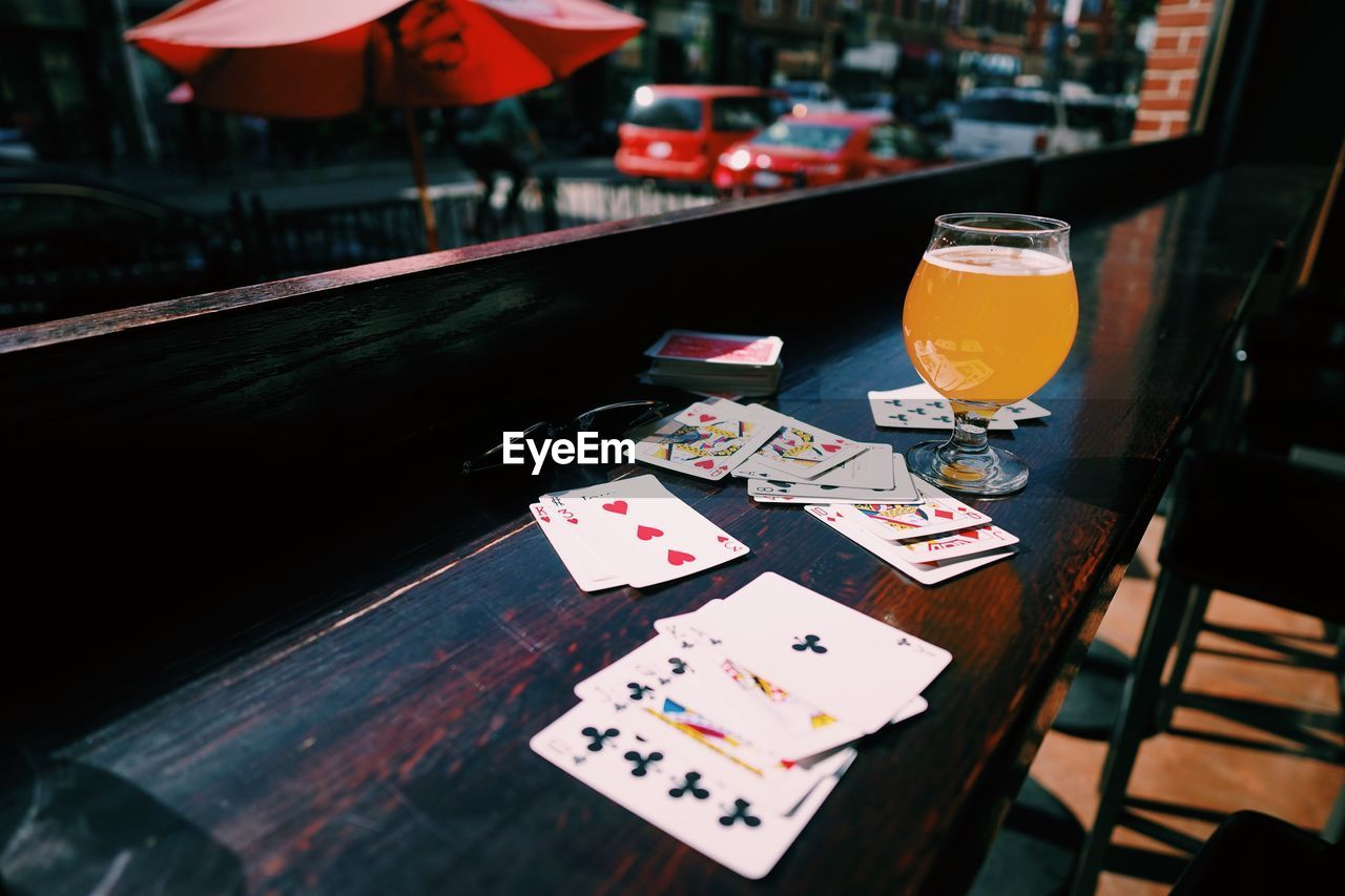 High Angle View Of Cards With Drinking Glass On Table At Cafe