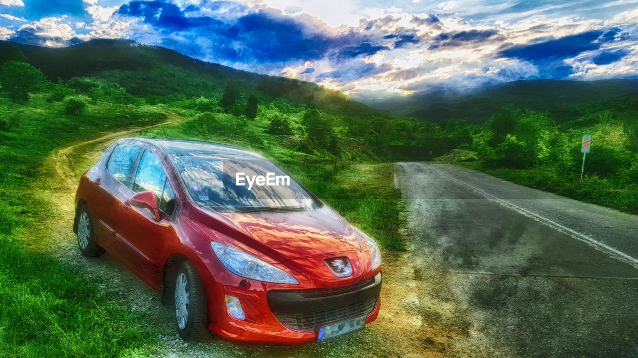 car, transportation, road, land vehicle, cloud - sky, mode of transport, landscape, day, tree, no people, outdoors, the way forward, sky, mountain, grass, nature