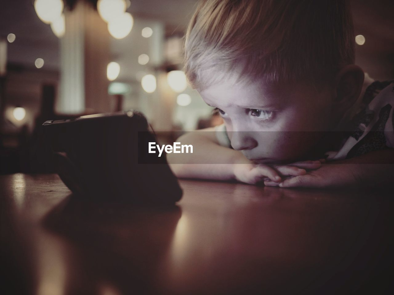 8close-Up Of Boy Using Phone On Table