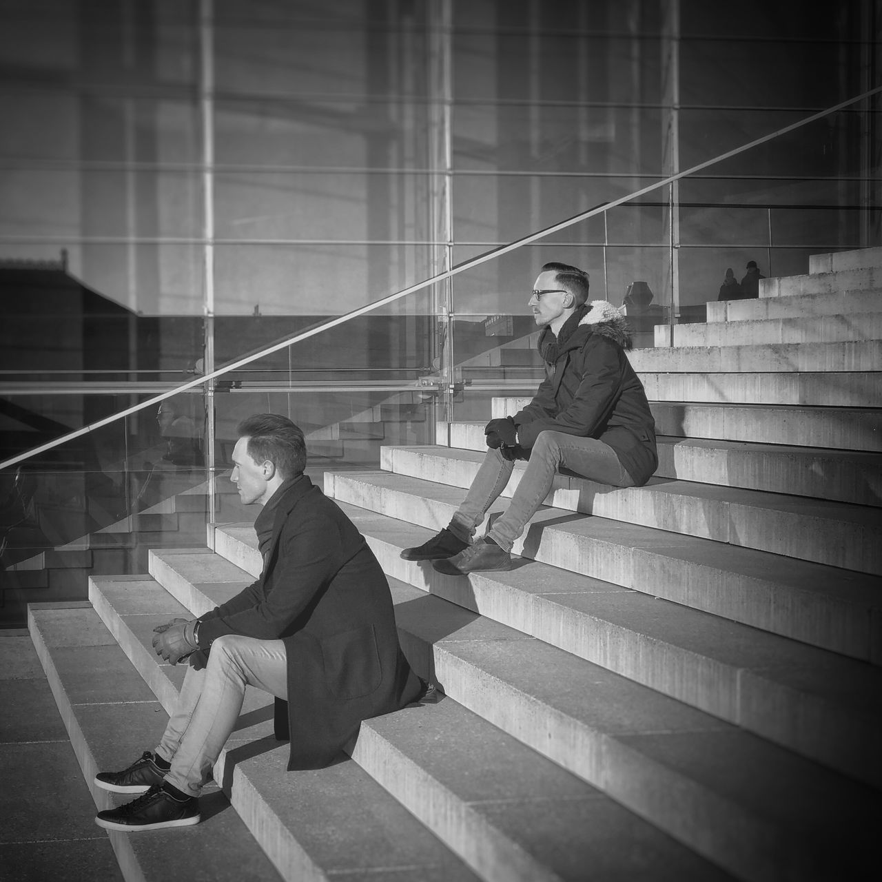 Fashionable Men Sitting On Steps Against Modern Building