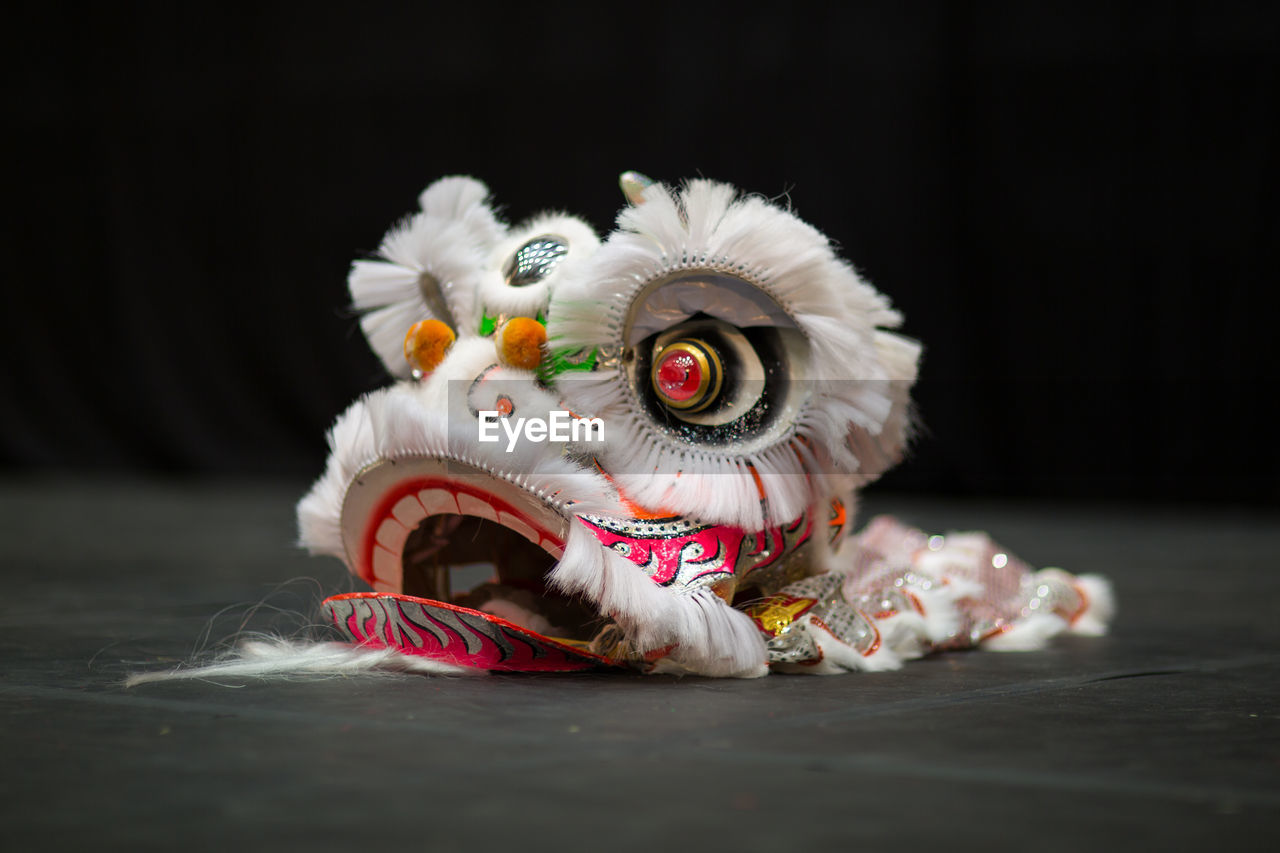 Close-Up Of Lion Dancing Costume On Table Against Black Background