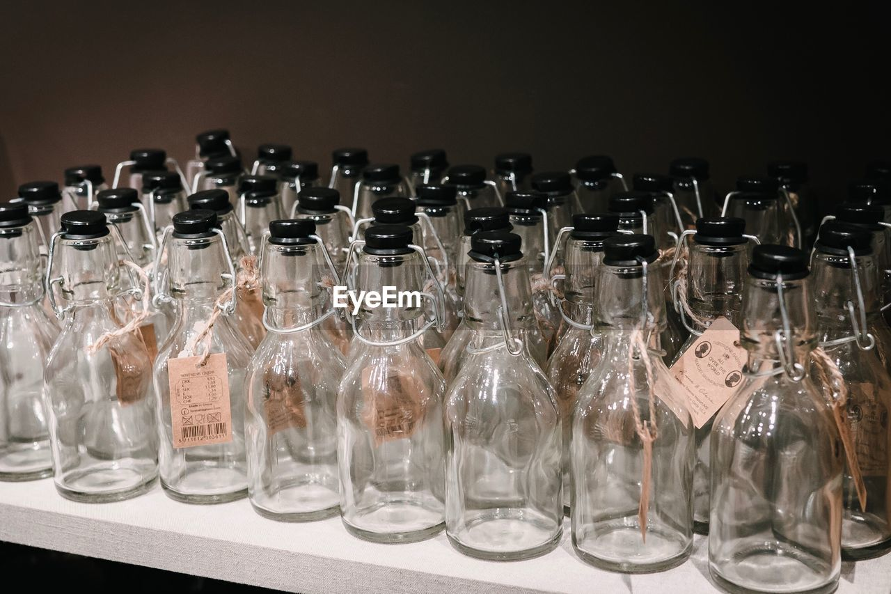 glass - material, transparent, large group of objects, indoors, no people, in a row, arrangement, close-up, container, still life, order, side by side, bottle, empty, technology, glass, healthcare and medicine, research, abundance, variation