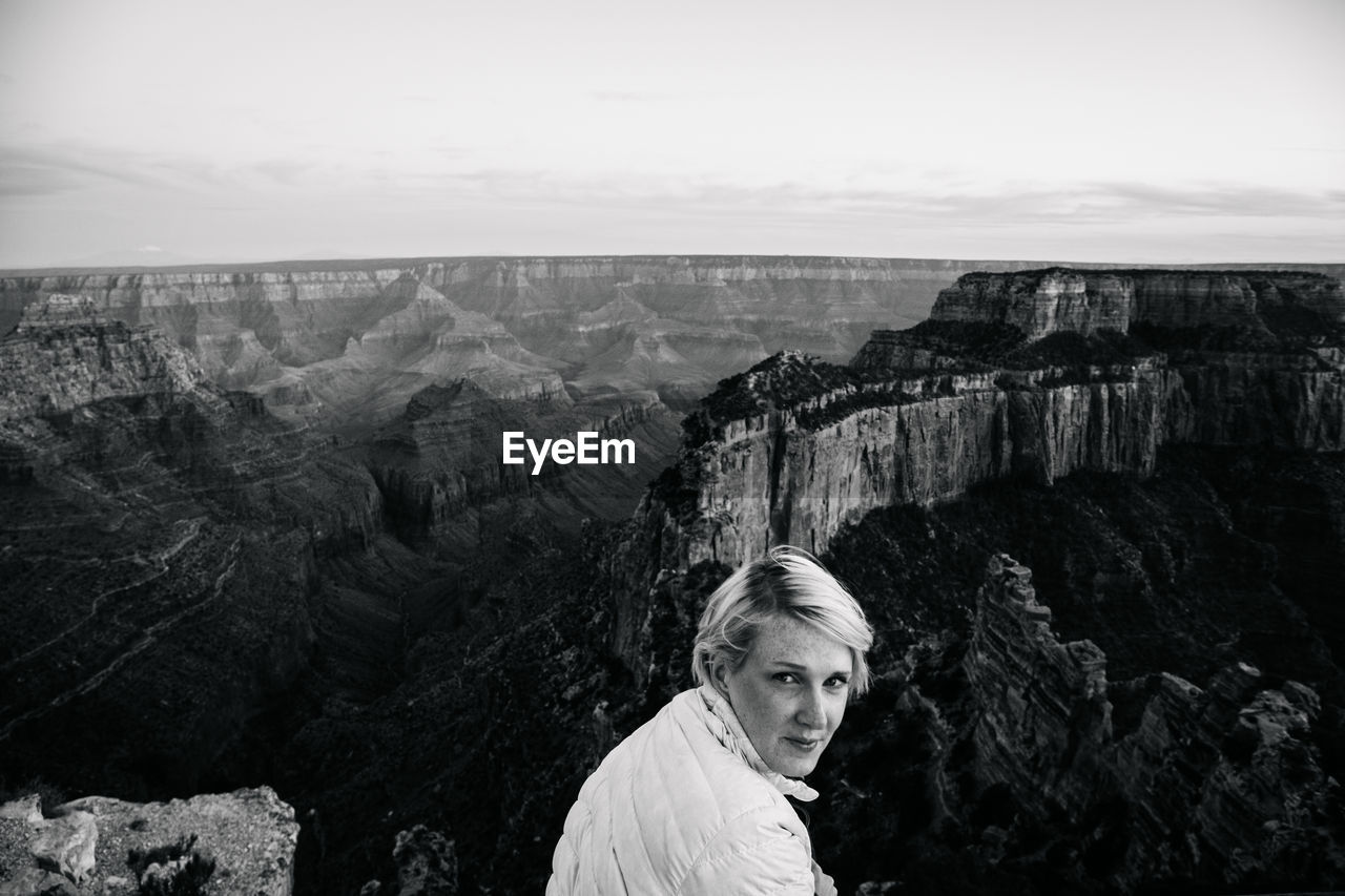 Portrait Of Woman By Rocky Mountains At Grand Canyon Against Sky