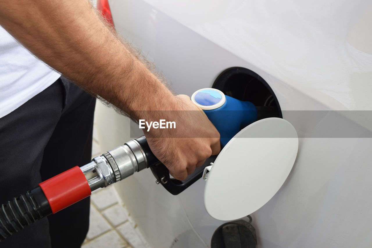 Midsection of man refueling car at gas station
