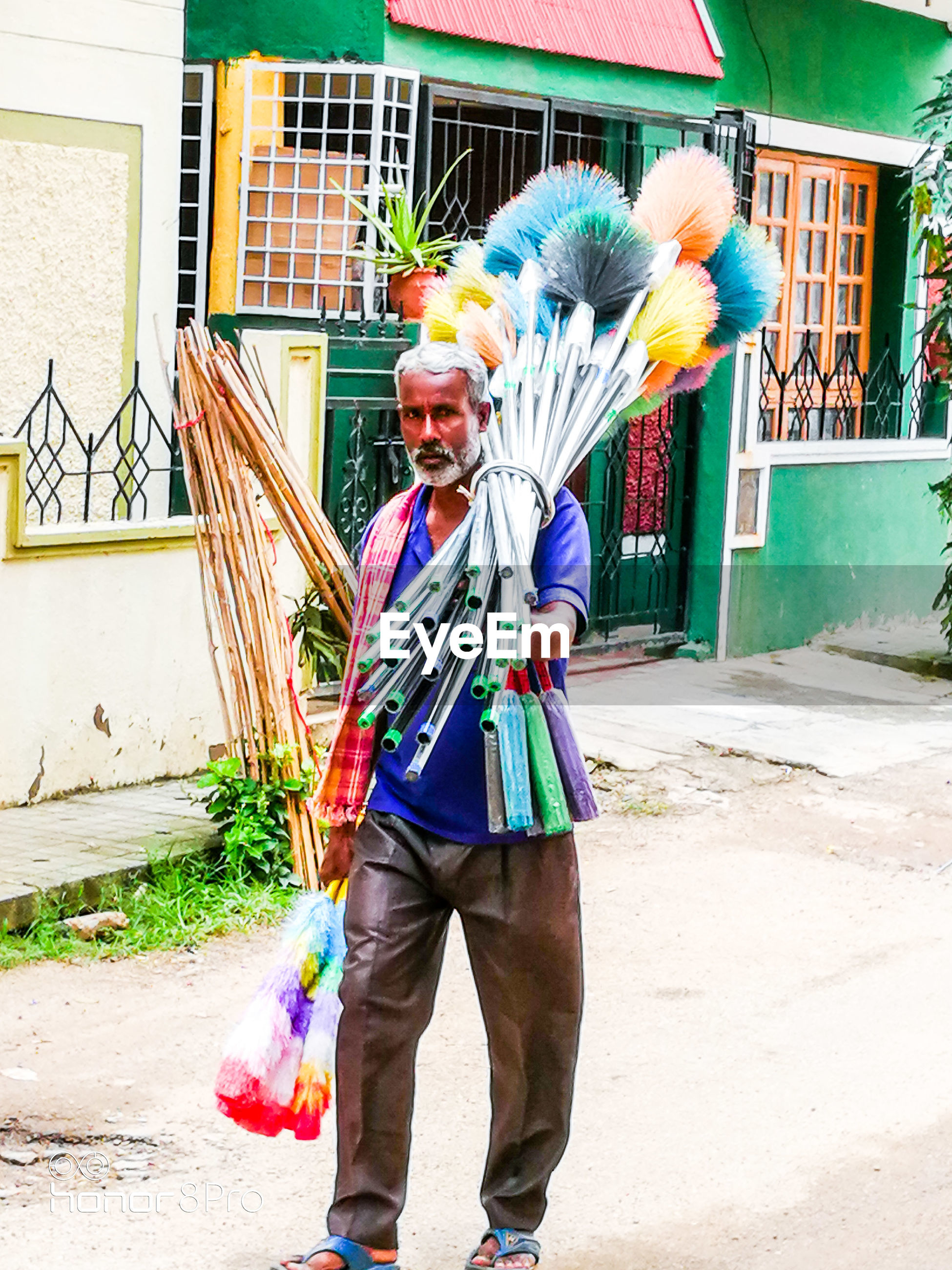Portrait of man selling brooms in market