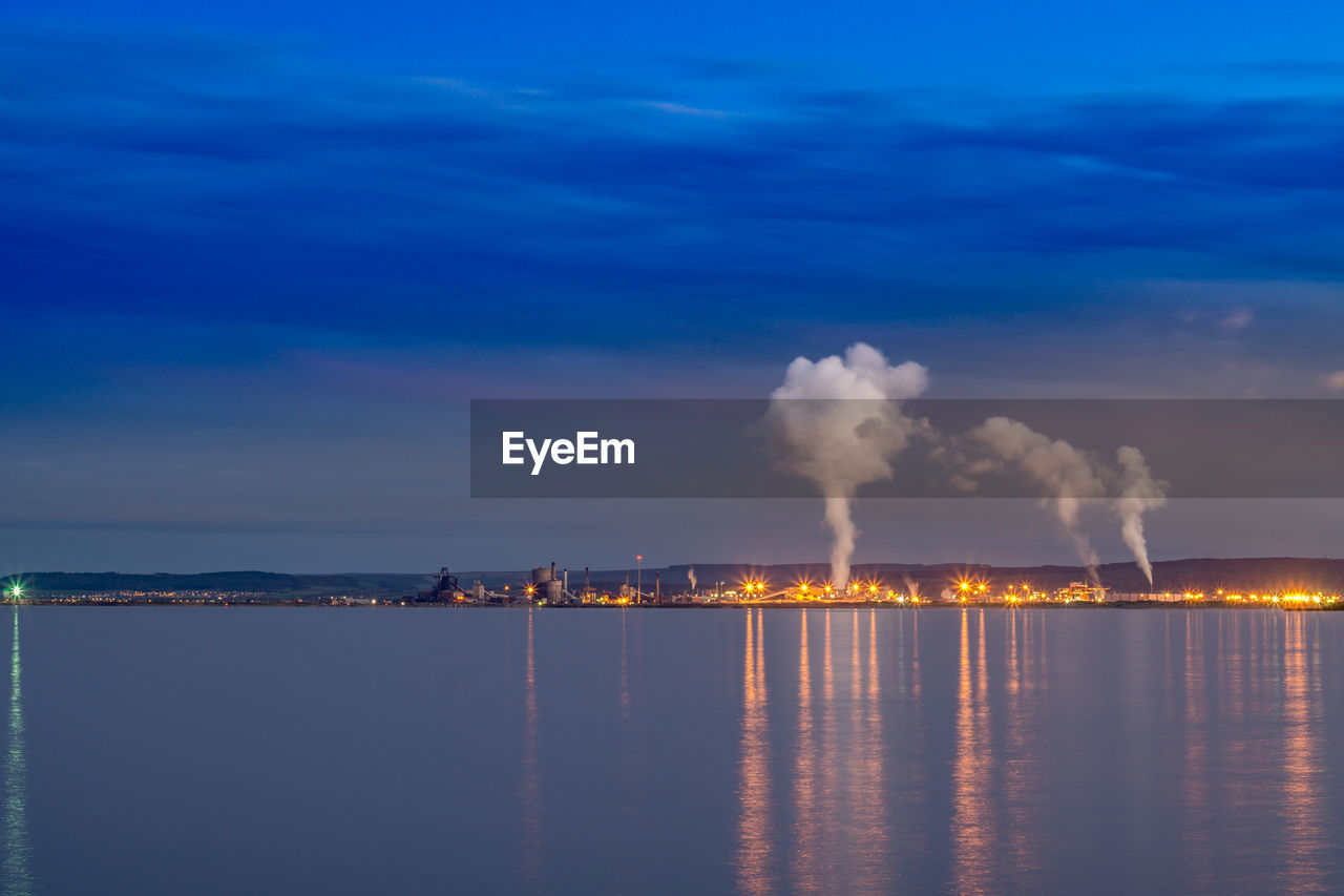 sky, water, building exterior, industry, waterfront, factory, nature, smoke - physical structure, pollution, architecture, cloud - sky, built structure, smoke stack, sea, environmental issues, environment, no people, emitting, blue, outdoors, fumes, air pollution, ecosystem, atmospheric, power in nature