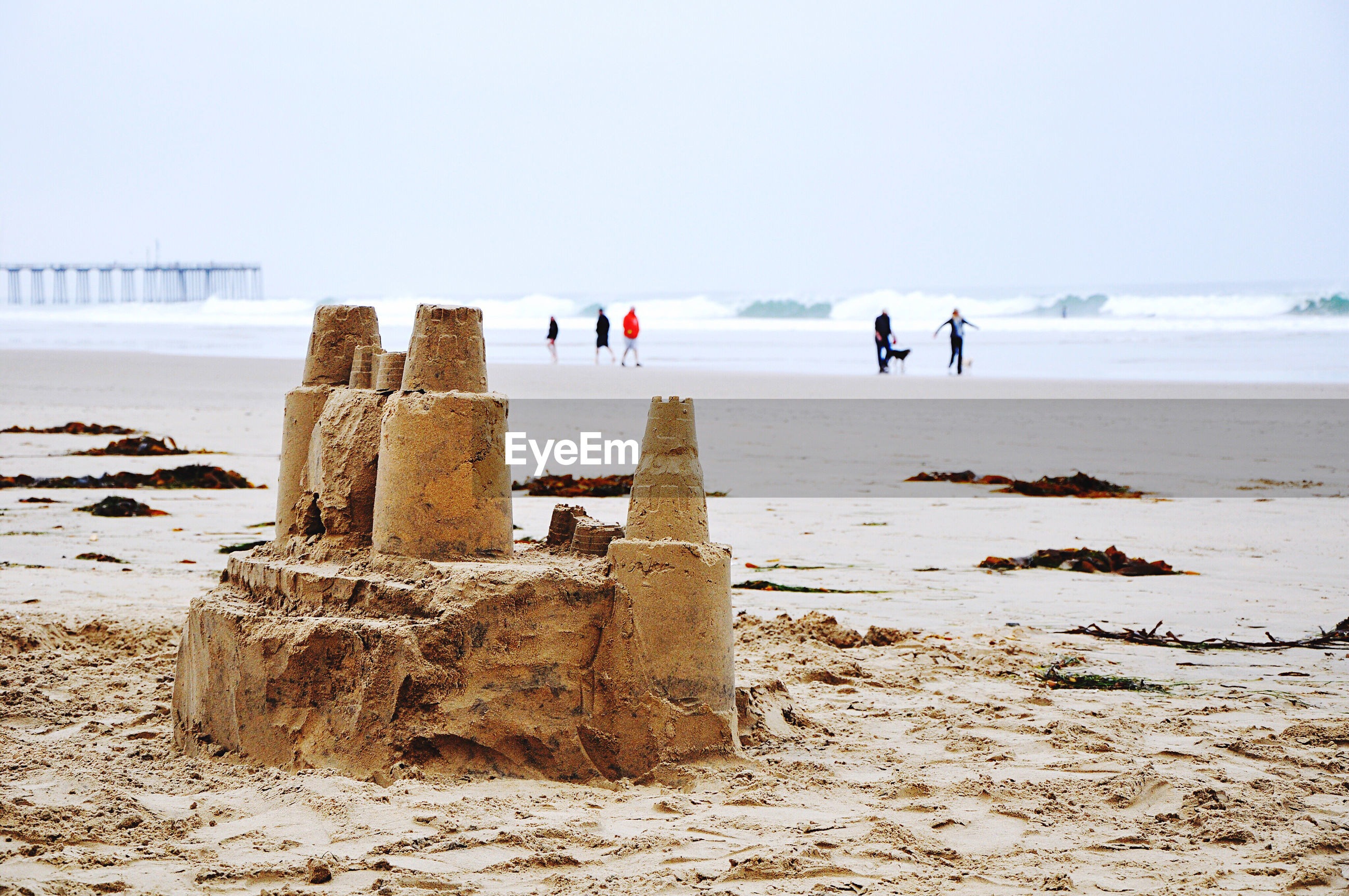 Sandcastle and people at beach against clear sky during winter