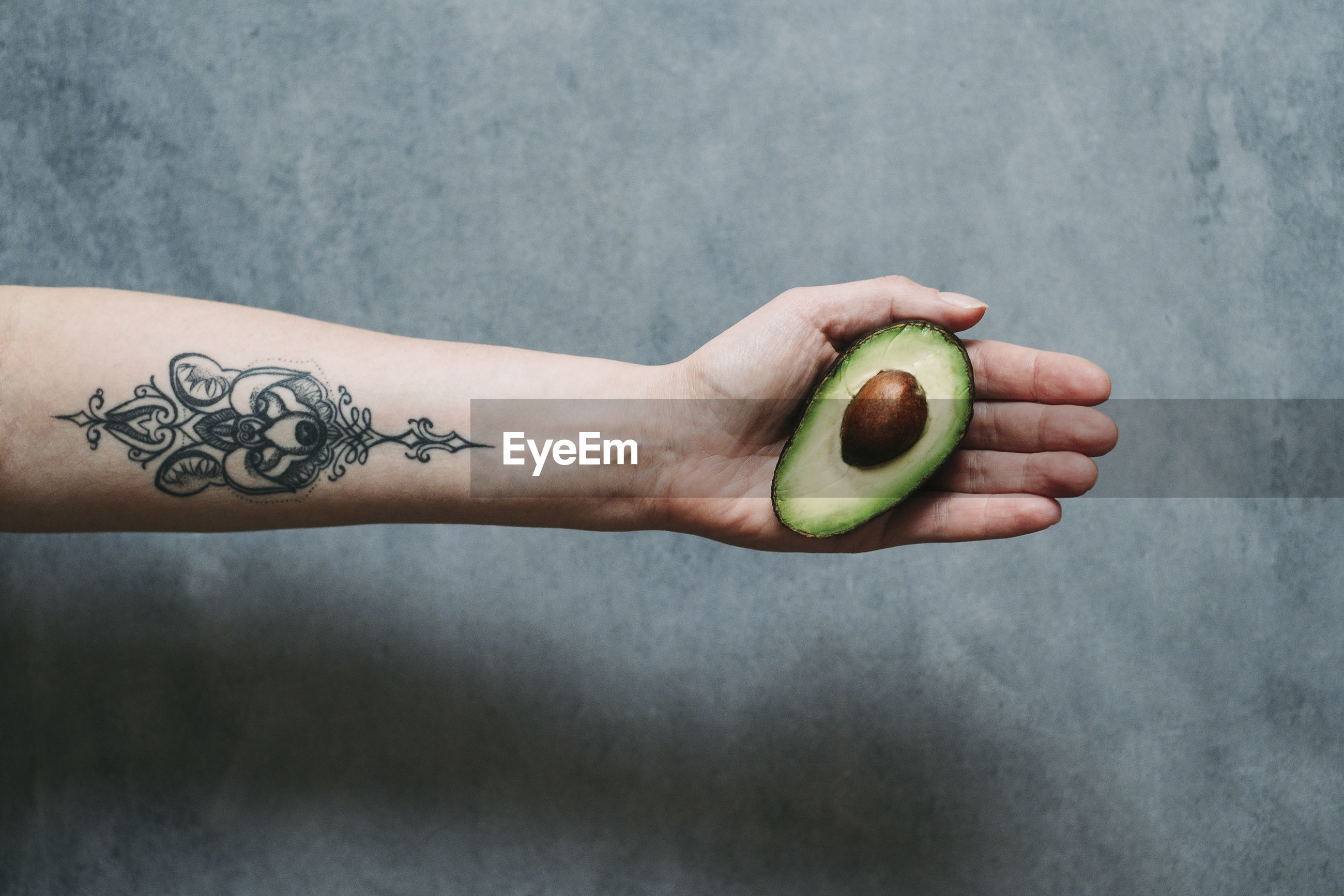 Cropped hand holding avocado against wall