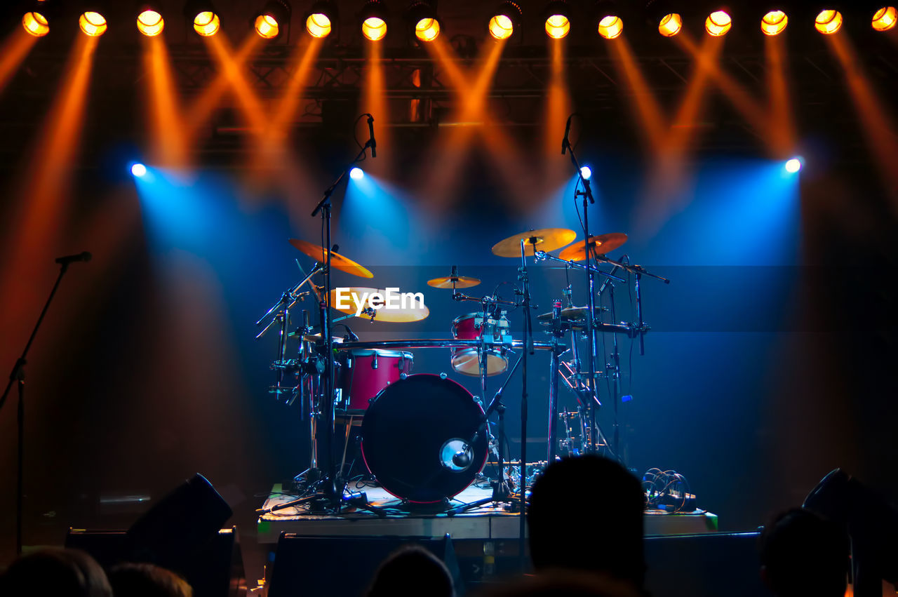 Illuminated Lights Falling On Drums At Stage During Music Concert