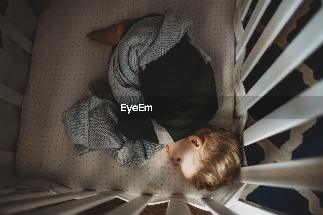 HIGH ANGLE VIEW OF BOY SLEEPING IN BED AT HOME