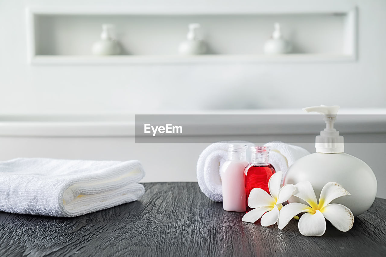 indoors, still life, flower, flowering plant, white color, no people, table, close-up, container, focus on foreground, bottle, home, vulnerability, nature, fragility, domestic room, plant, home interior, towel, wood - material