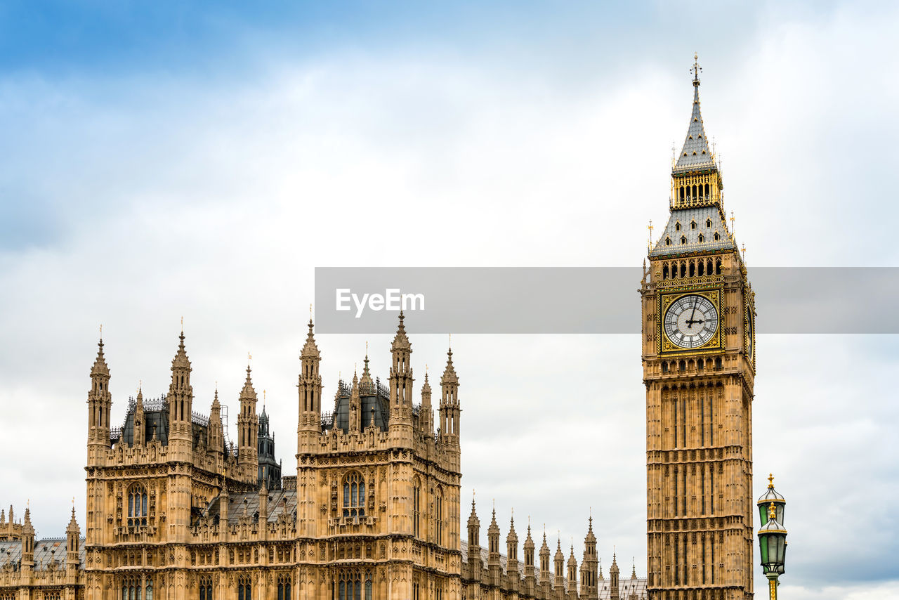 Big ben and palace of westminster against cloudy sky in city