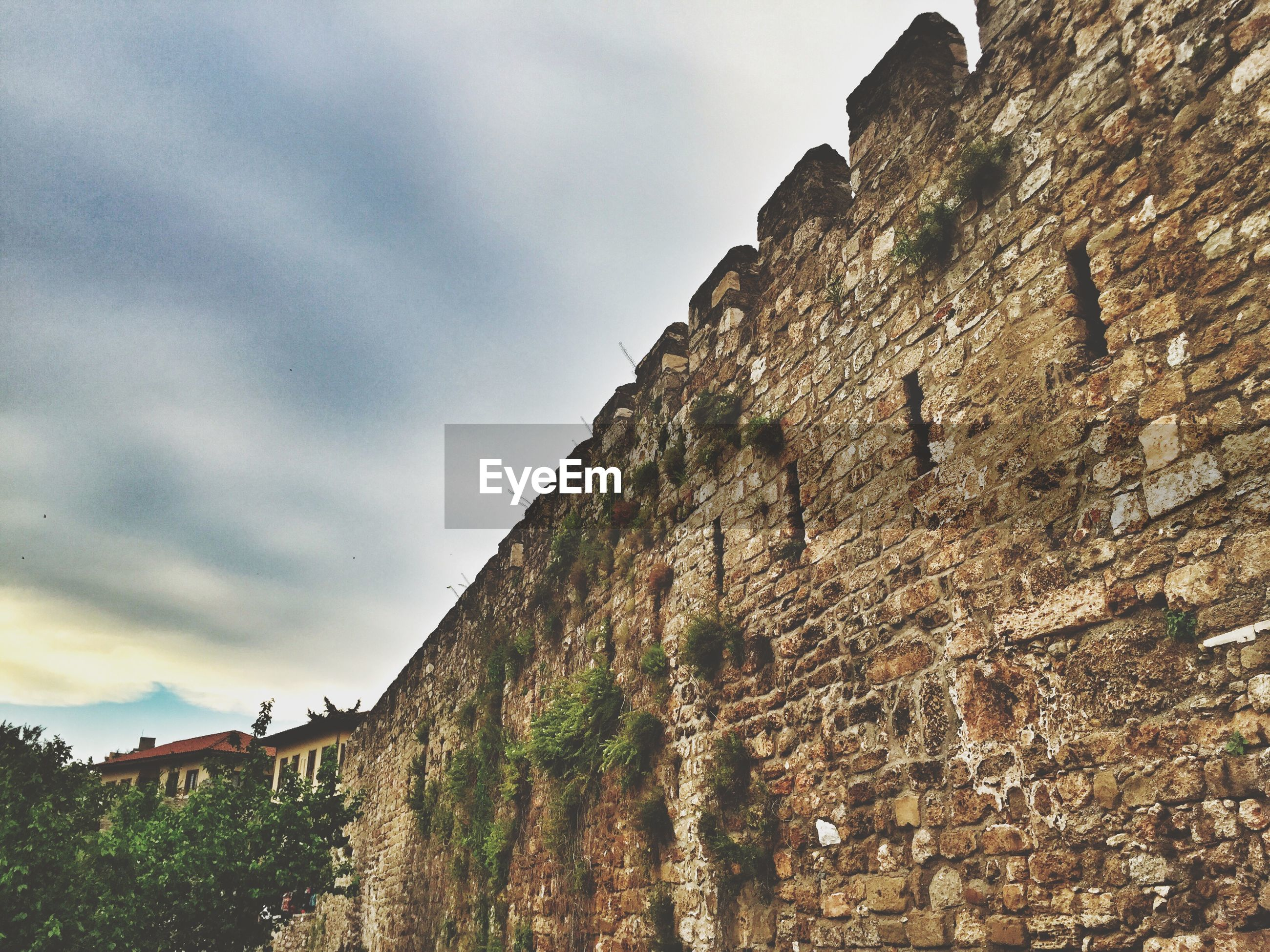 Low angle view of historic stone wall at kaleici against cloudy sky
