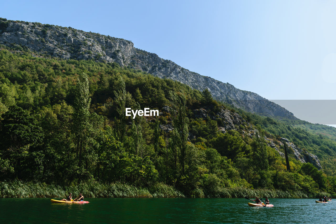 People rafting in river by mountains against clear sky