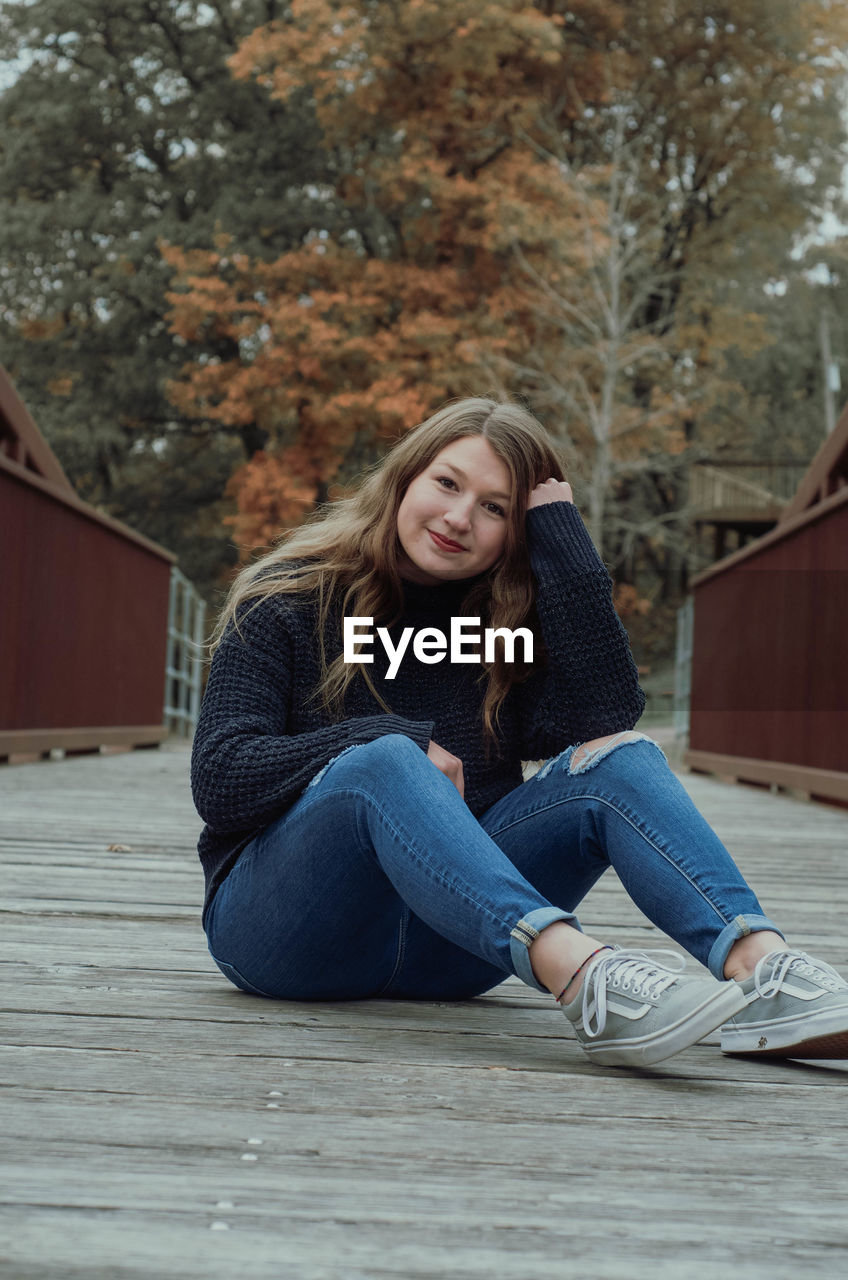 Portrait of smiling girl sitting on wooden footbridge
