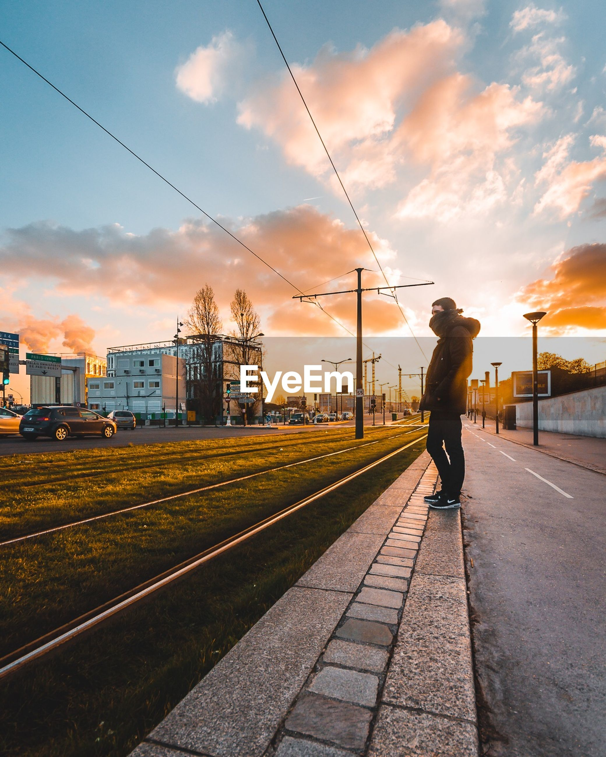 sky, cloud - sky, transportation, sunset, full length, railroad track, one person, rail transportation, mode of transport, real people, outdoors, cable, men, built structure, electricity pylon, architecture, nature, one man only, day, people