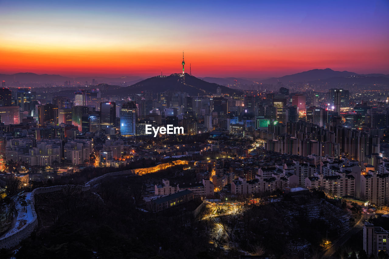 Aerial view of illuminated city during sunset