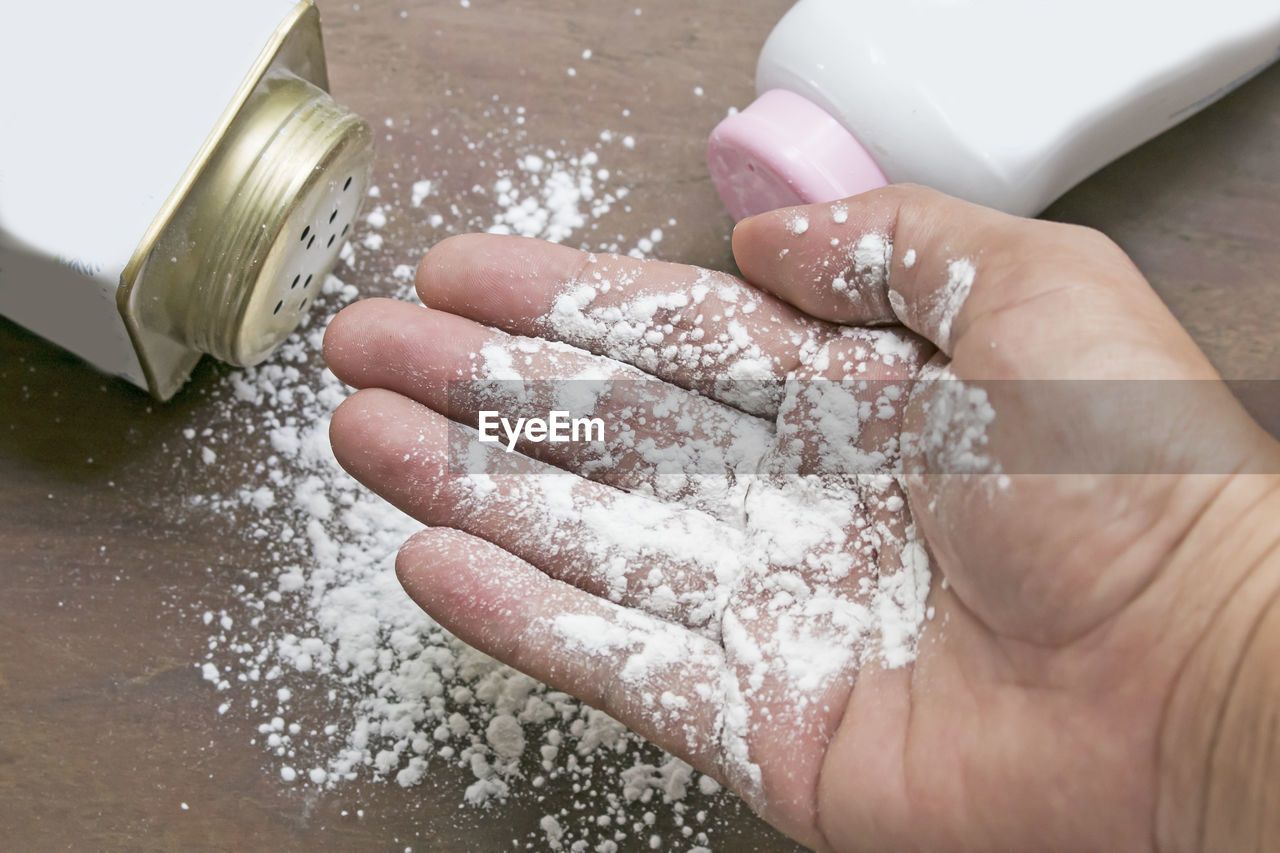 Cropped hand holding talcum powder