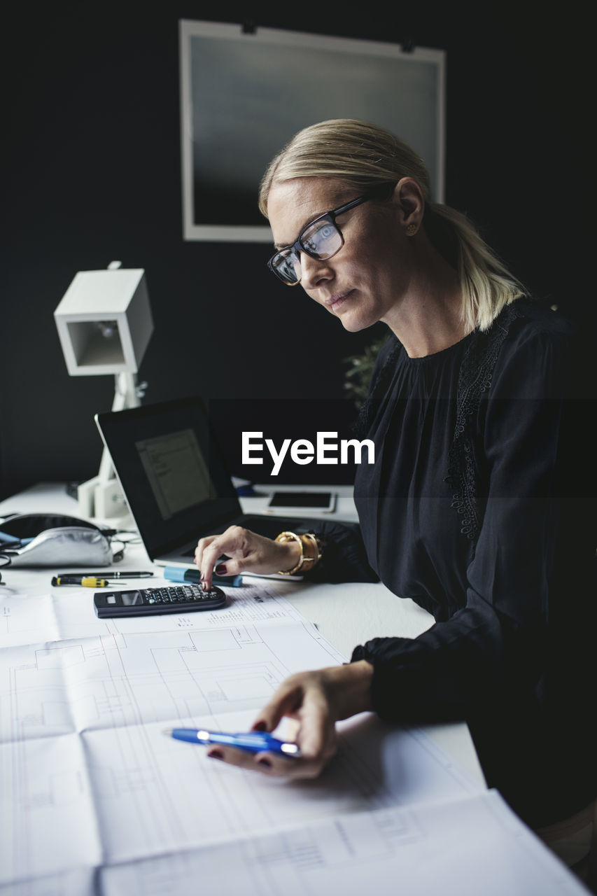 table, computer, glasses, business, eyeglasses, office, furniture, indoors, desk, adult, concentration, technology, one person, business person, waist up, sitting, women, real people, wireless technology