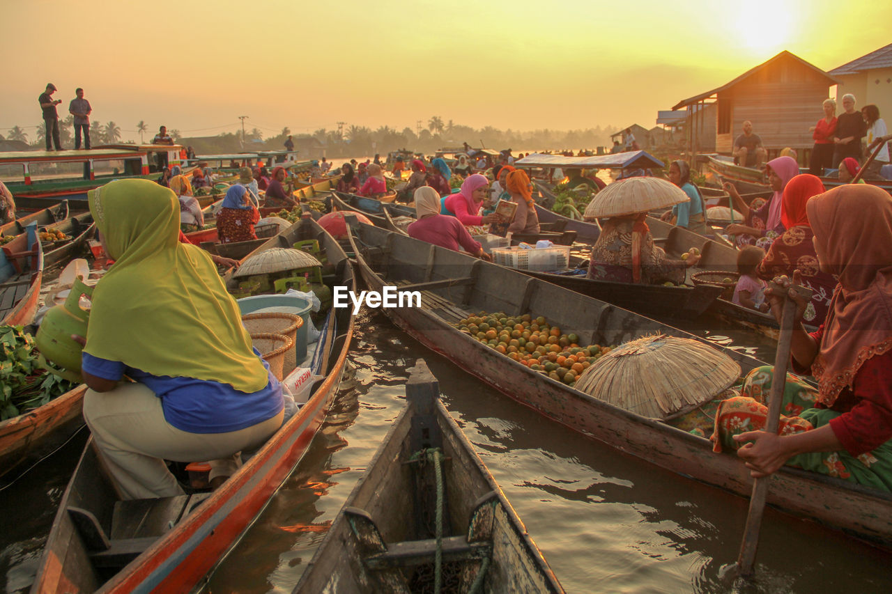 People Selling Food In Boats On Lake During Sunset