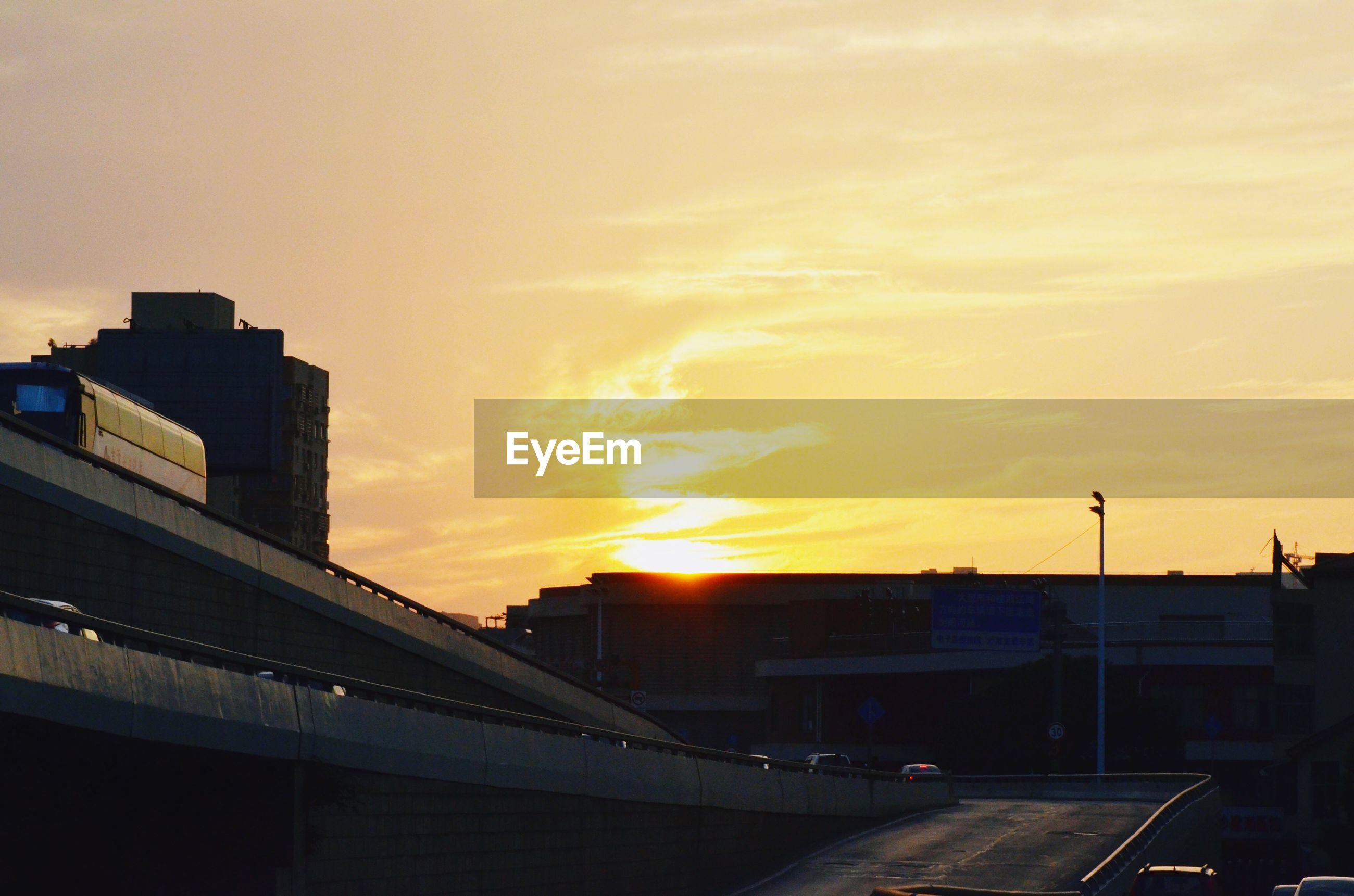 Bridge in city during sunset