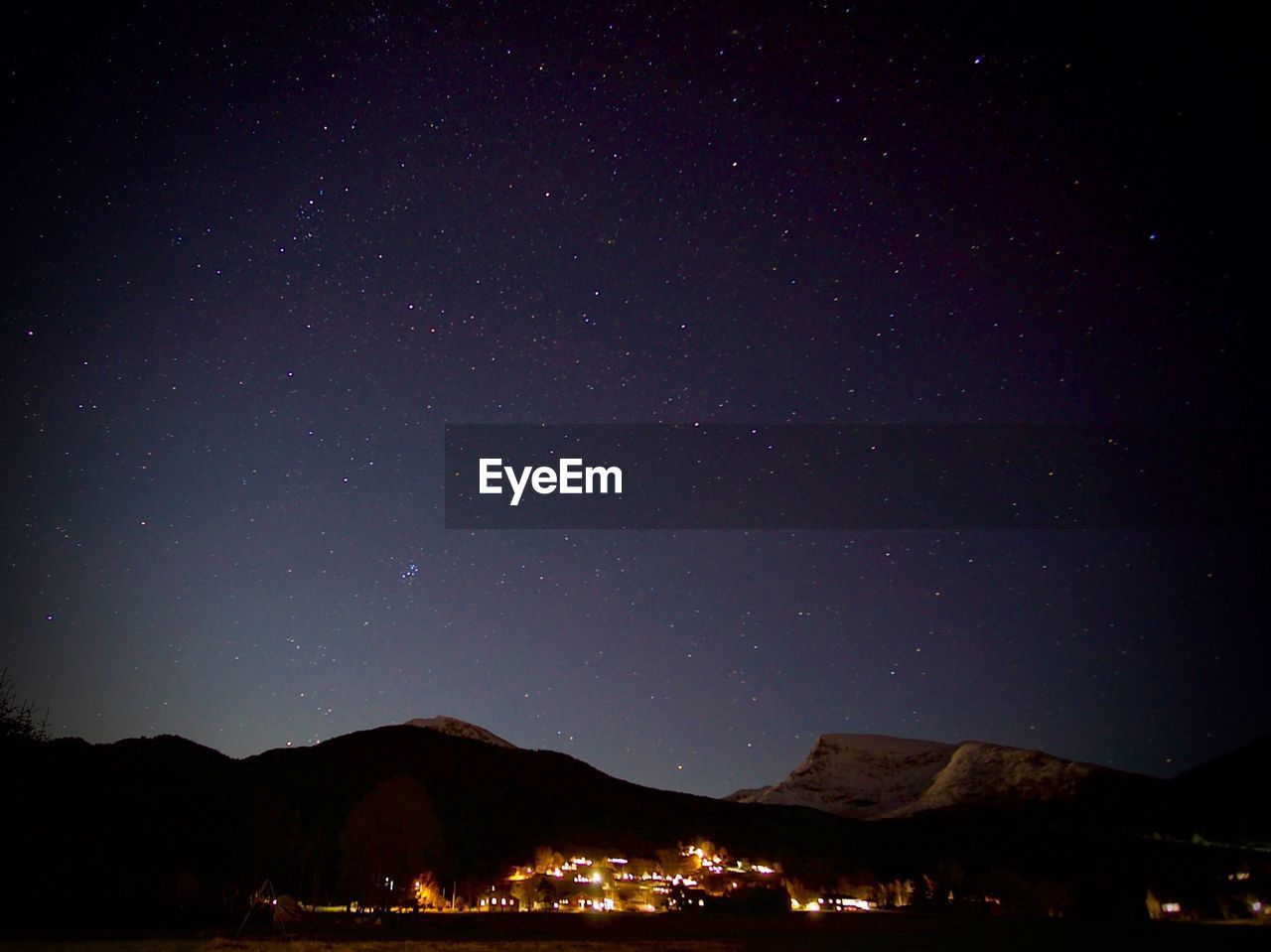 SCENIC VIEW OF ILLUMINATED MOUNTAINS AGAINST STAR FIELD