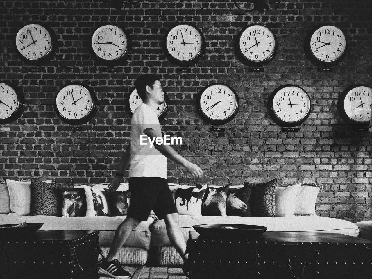 Man walking by wall clocks at home