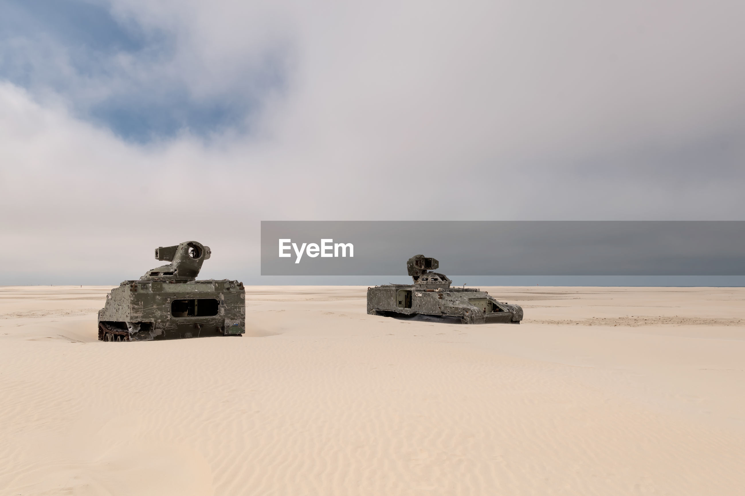 Abandoned armored tanks at desert against cloudy sky