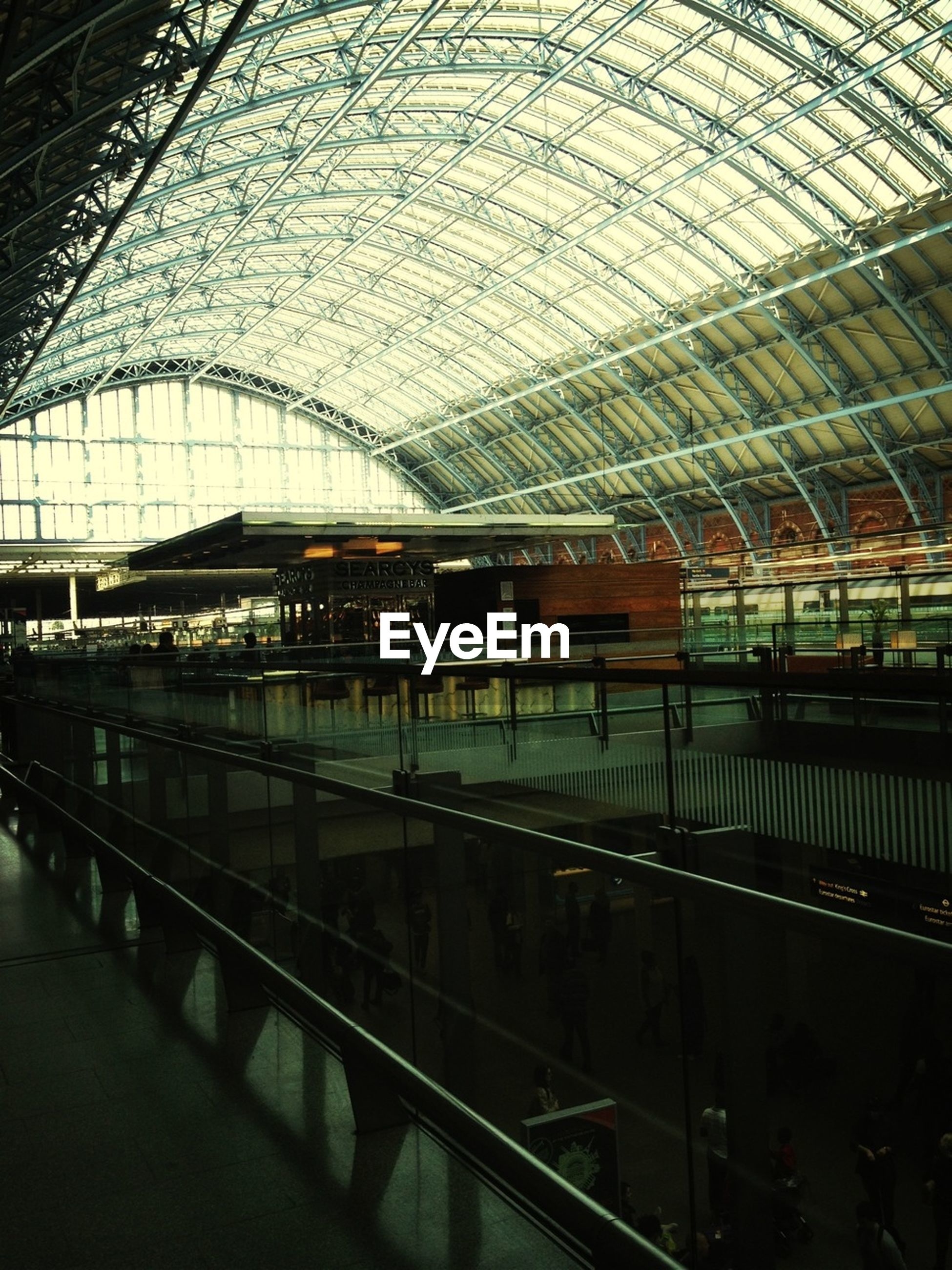 indoors, railroad station, ceiling, rail transportation, public transportation, railroad station platform, railroad track, transportation, architecture, built structure, travel, illuminated, interior, incidental people, subway station, train - vehicle, transportation building - type of building, architectural column, subway, high angle view