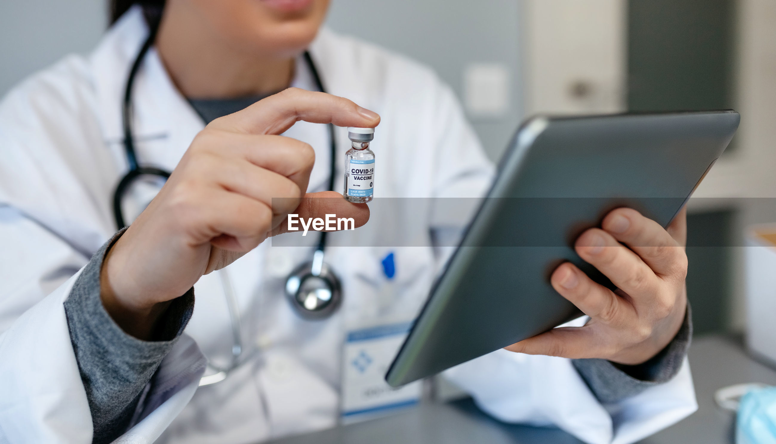 Midsection of doctor holding vaccine using digital tablet