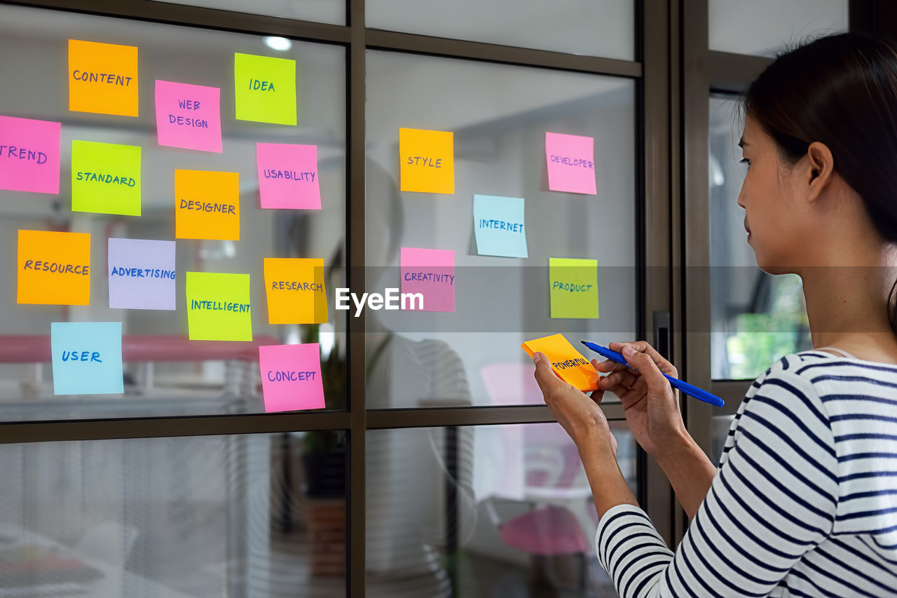 Businesswoman writing in adhesive note at office