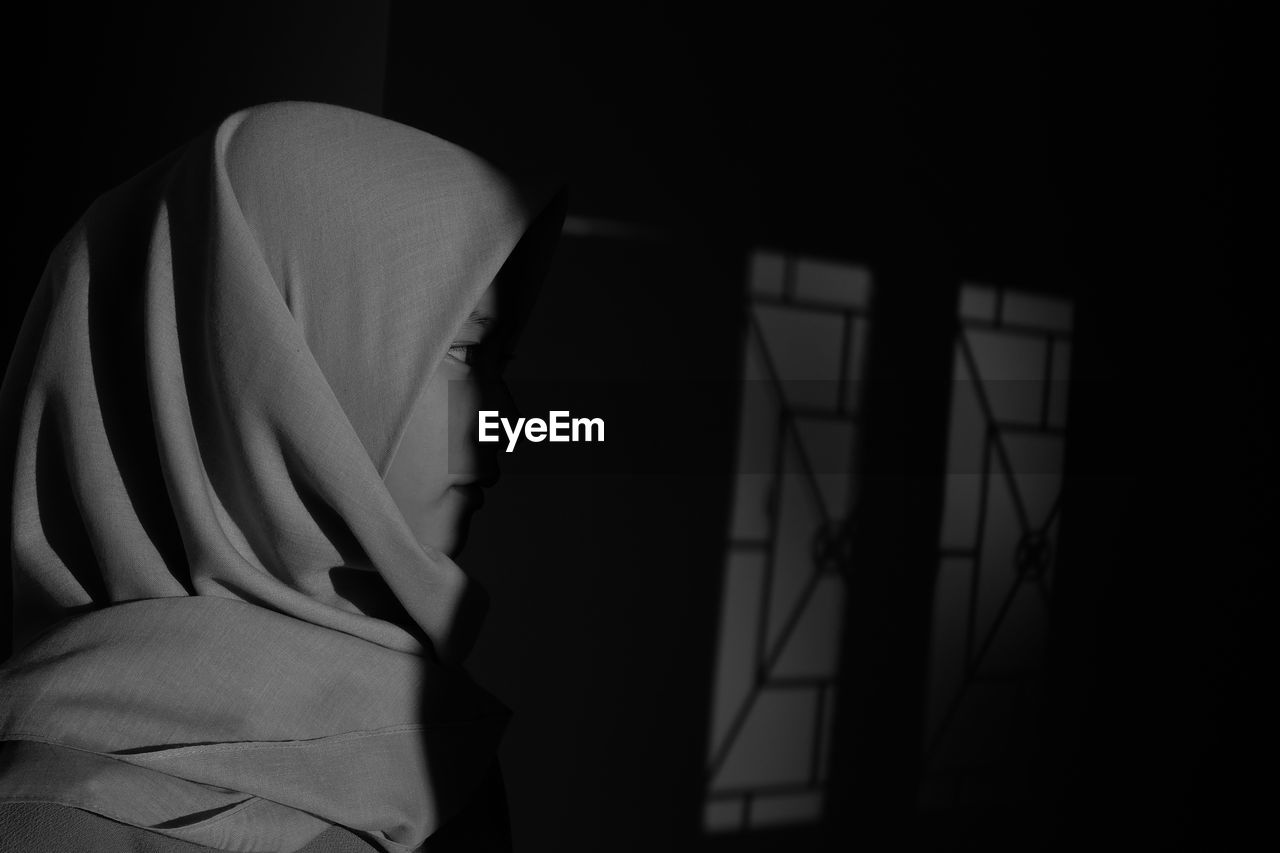Close-Up Of Woman Wearing Hijab Standing In Darkroom