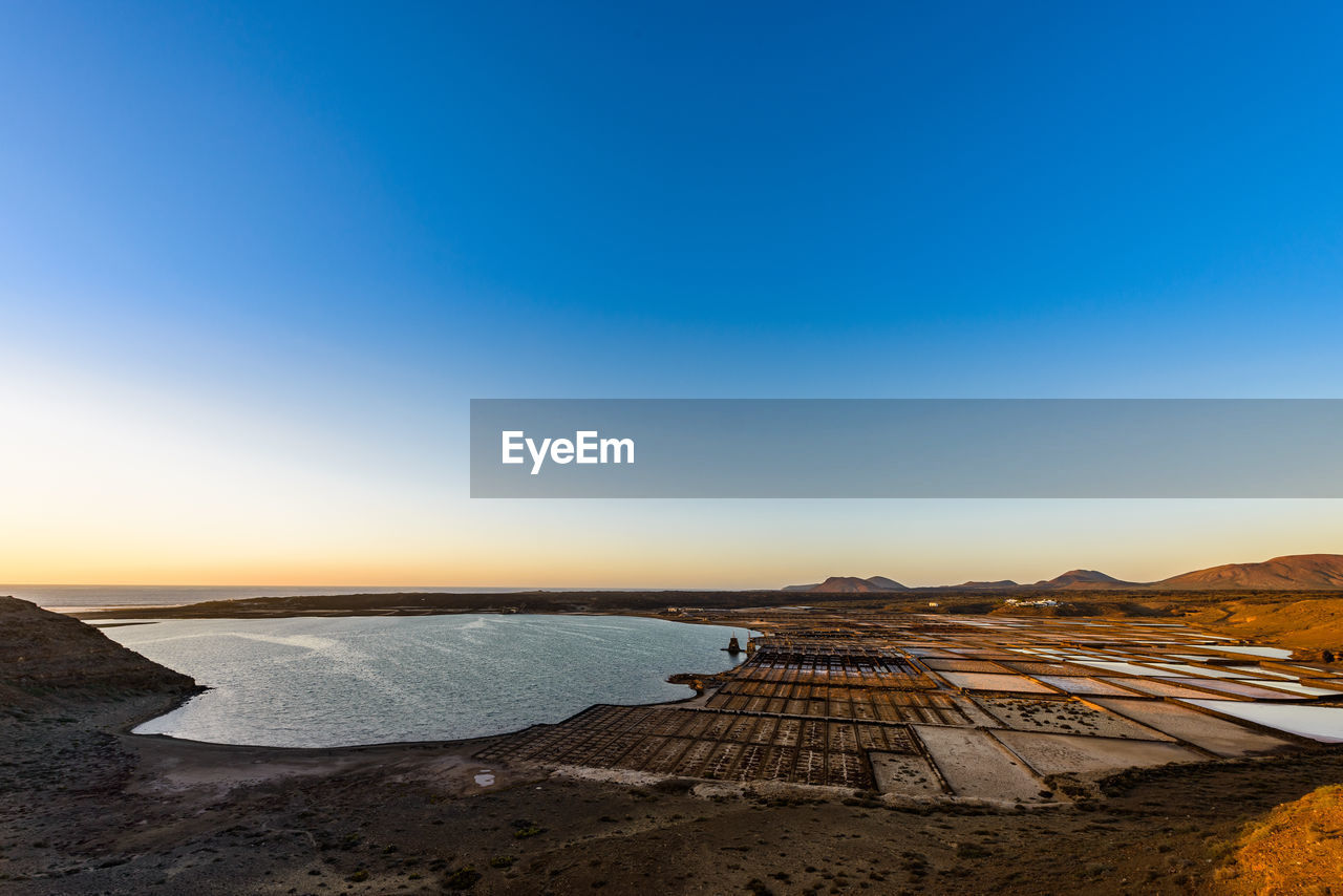Scenic view lanzarote salt basins against clear sky during sunset