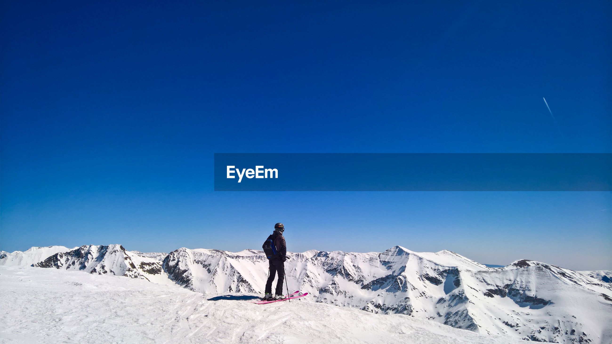 Man standing on snowcapped mountain against clear blue sky