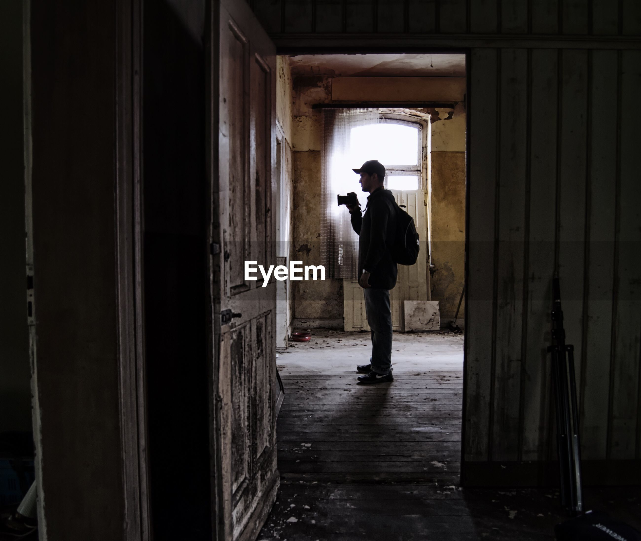 Side view of man standing with camera in abandoned house
