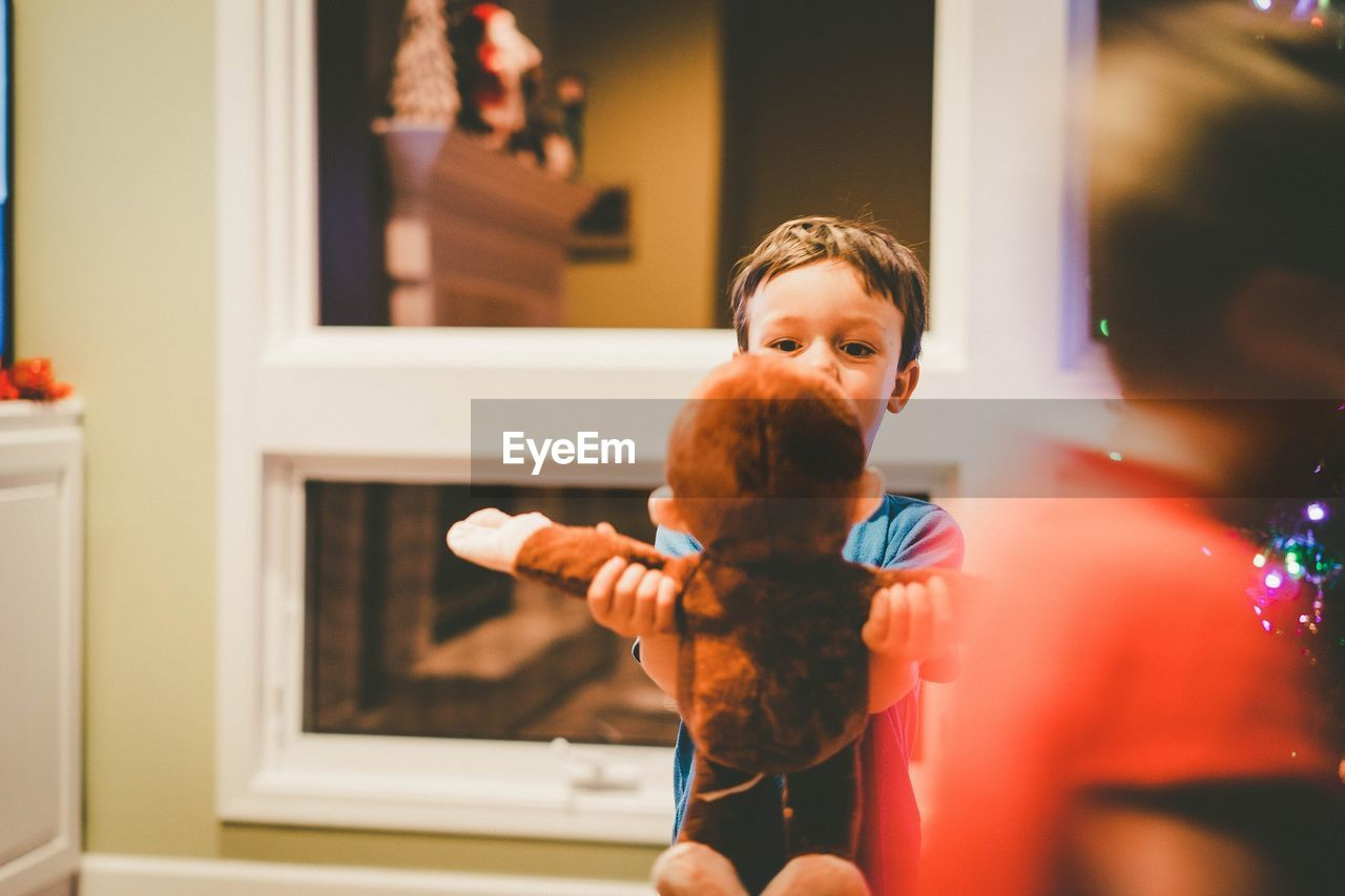 Boy holding monkey toy at home