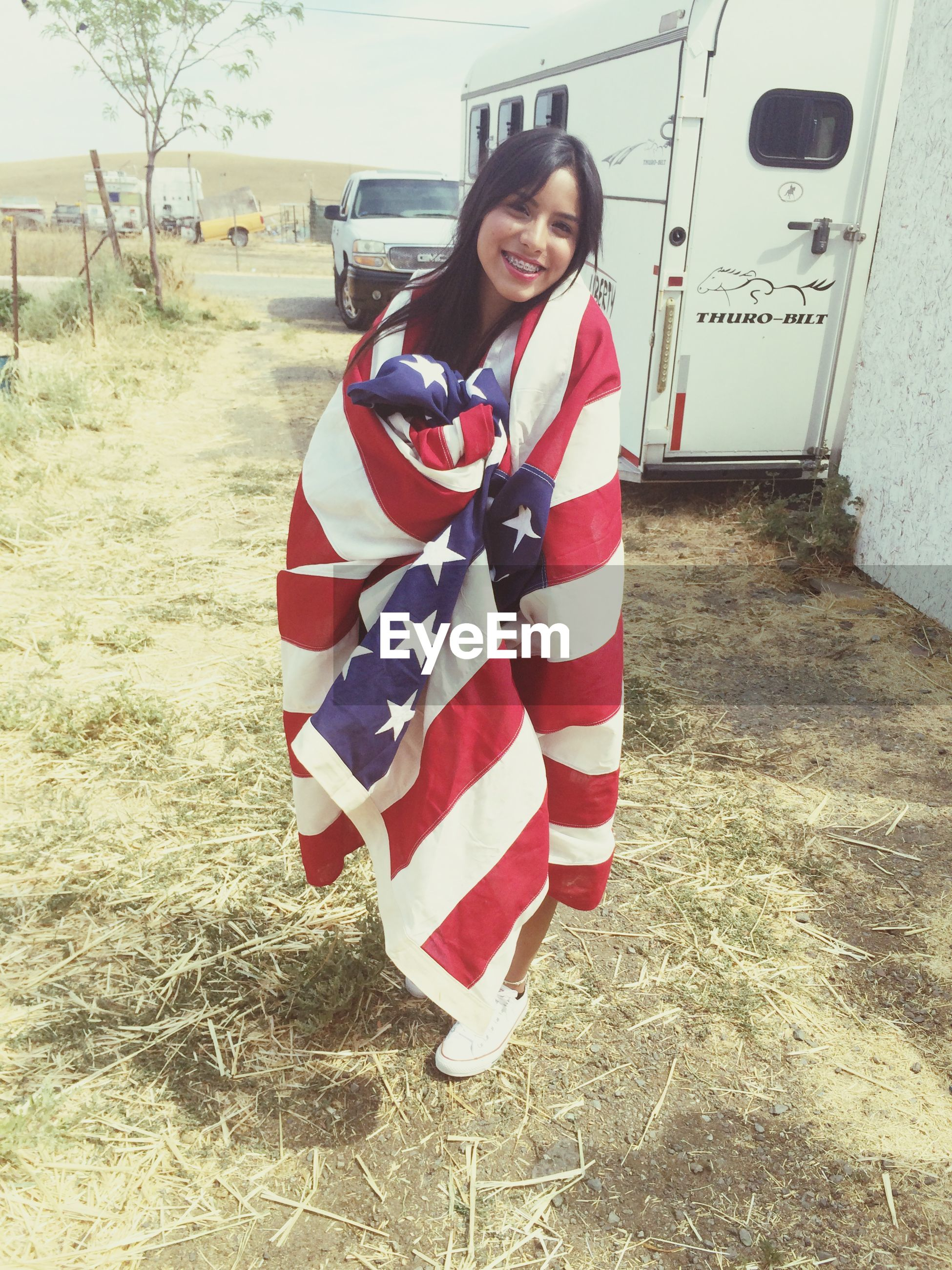 red, person, lifestyles, front view, young adult, full length, casual clothing, leisure activity, portrait, patriotism, looking at camera, young women, striped, smiling, standing, happiness, flag, building exterior