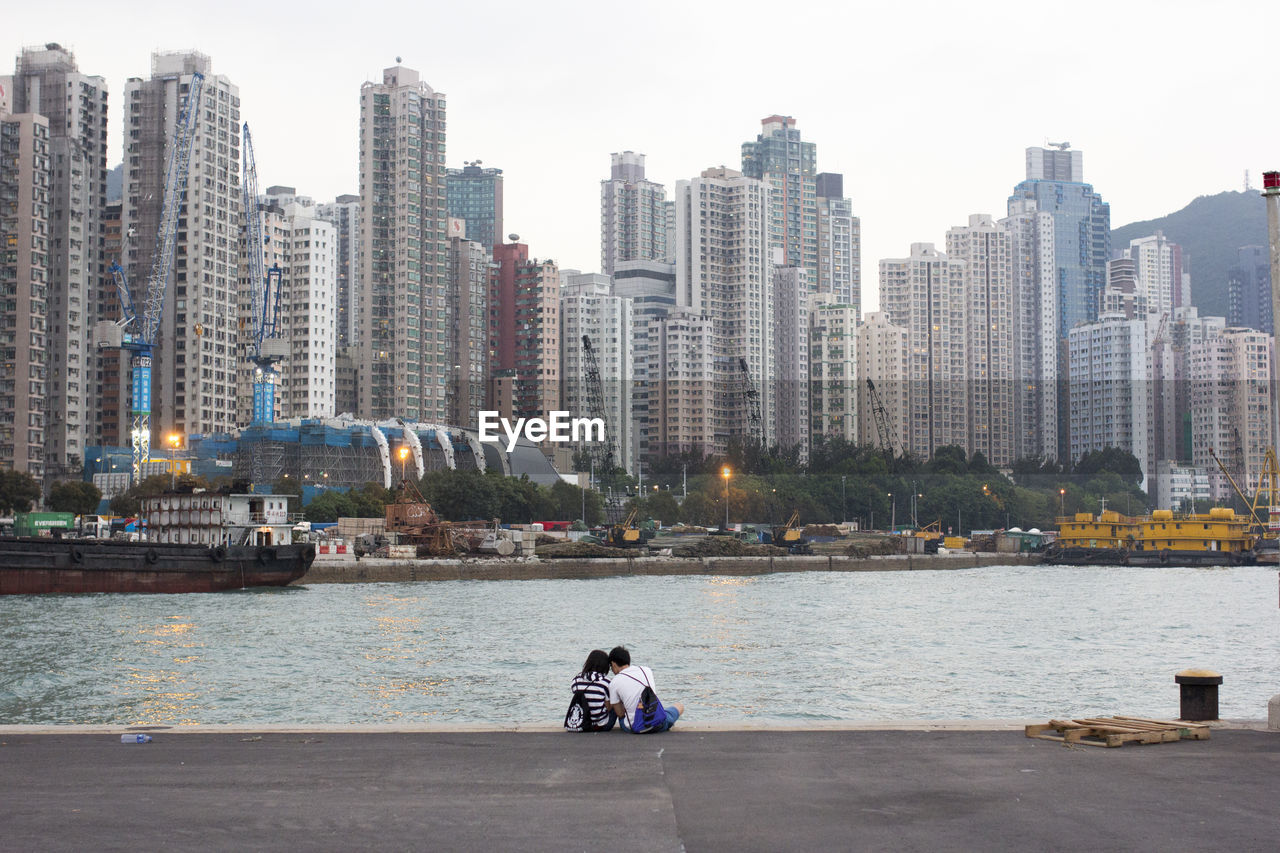 building exterior, architecture, built structure, real people, city, skyscraper, water, one person, cityscape, river, outdoors, lifestyles, day, full length, sitting, women, urban skyline, modern, nature, sky, people