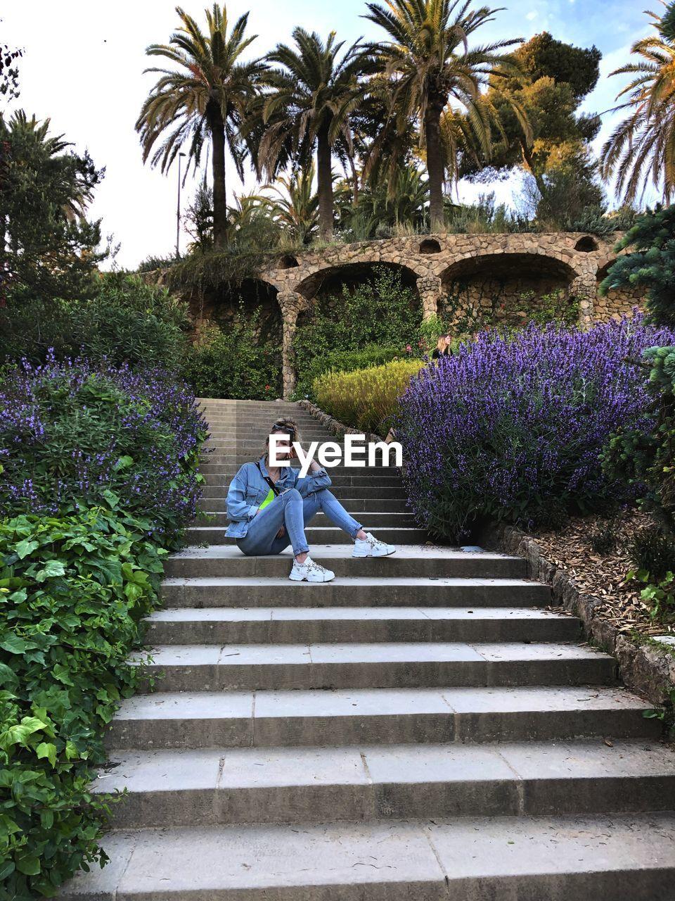 FULL LENGTH OF WOMAN SITTING ON PURPLE WALL