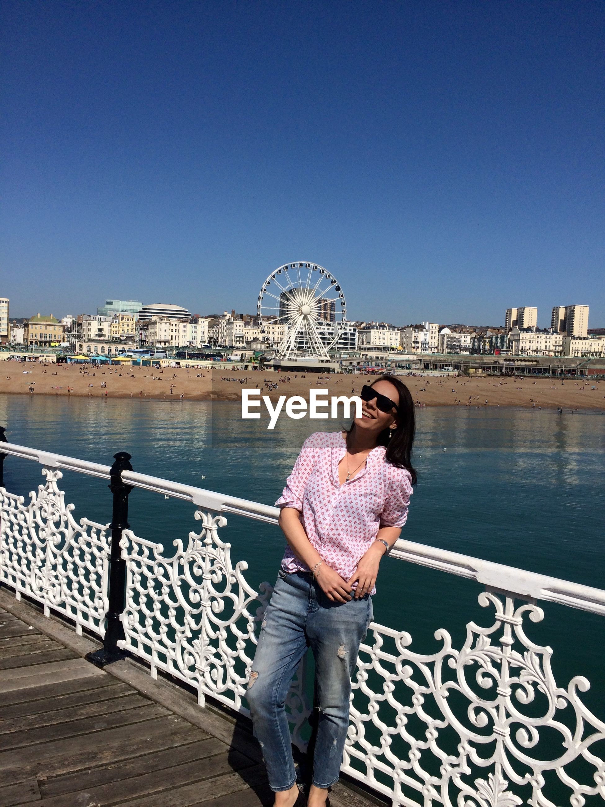 water, young adult, clear sky, lifestyles, casual clothing, built structure, standing, leisure activity, architecture, copy space, building exterior, person, full length, young women, blue, looking at camera, portrait, sea
