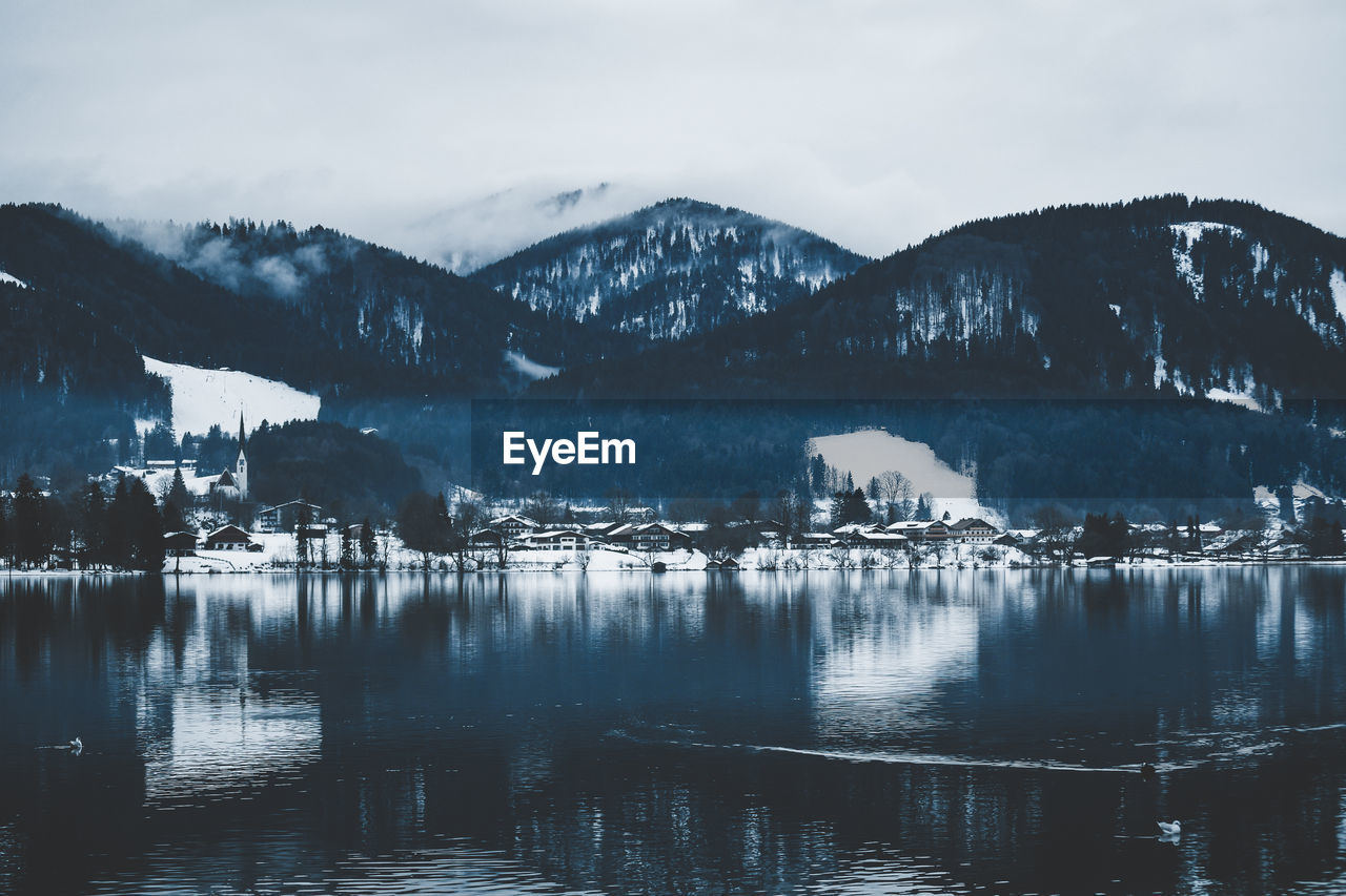water, mountain, sky, waterfront, scenics - nature, beauty in nature, mountain range, no people, cloud - sky, architecture, cold temperature, nature, tranquil scene, built structure, lake, building exterior, tranquility, winter, outdoors, snowcapped mountain