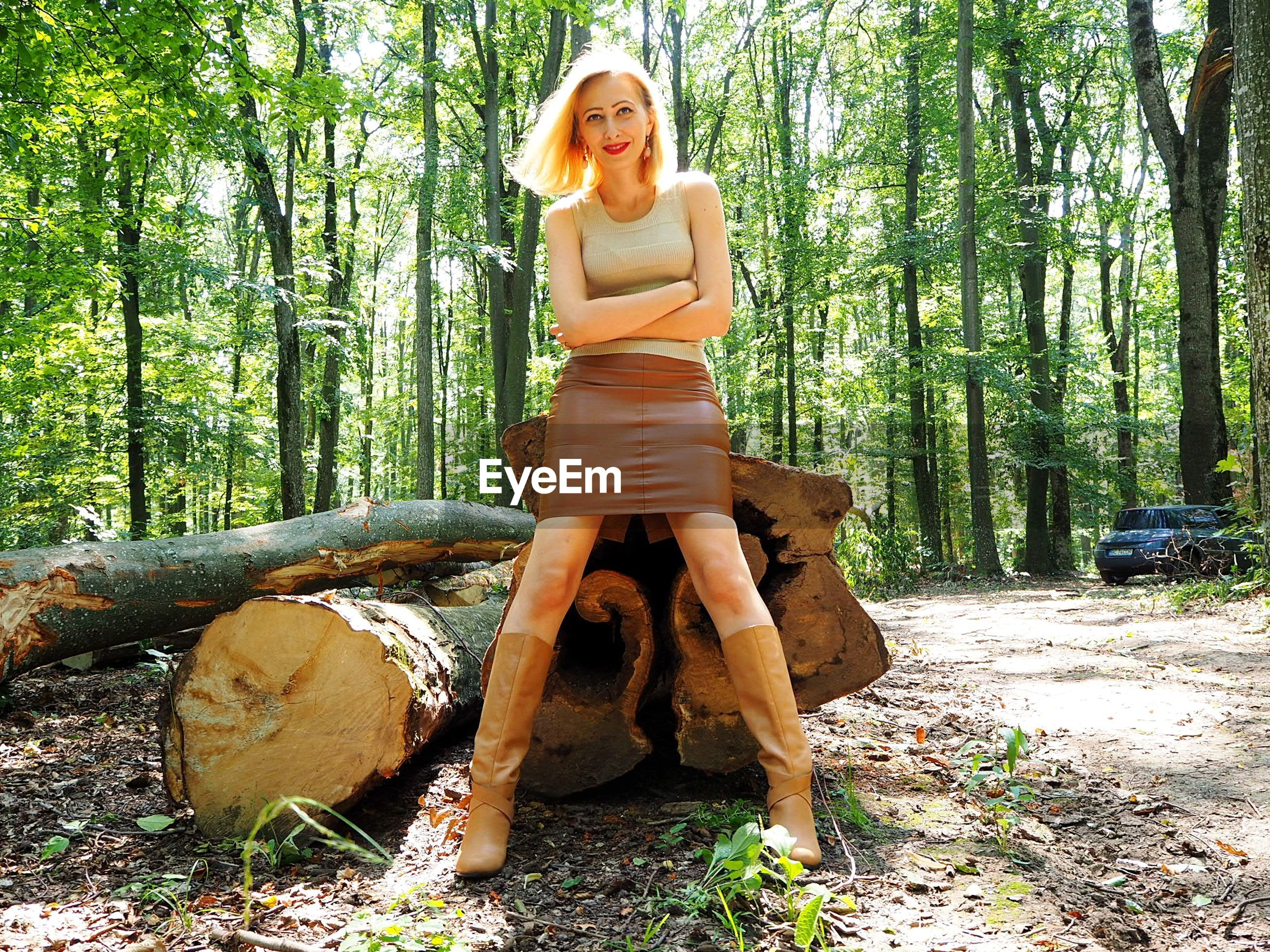 Portrait of woman standing against tree stump at forest