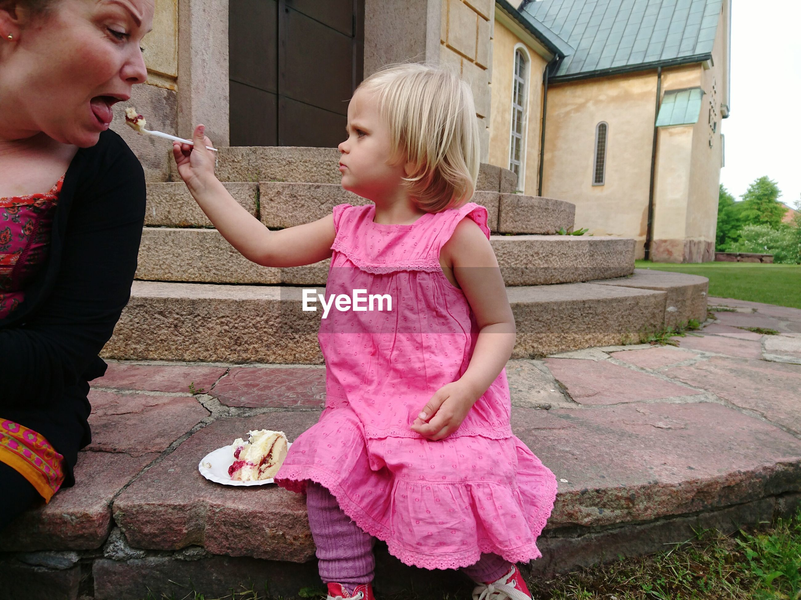 Portrait of cute girl feeding cake to woman