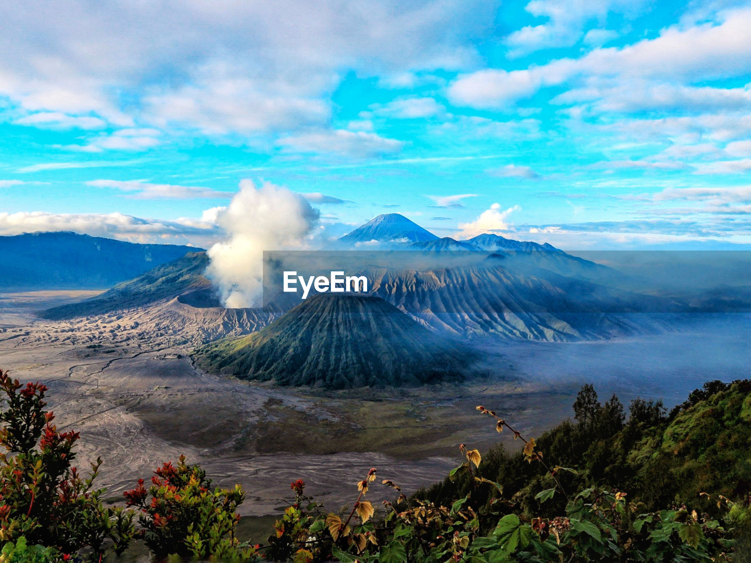View of volcanic mountains against cloudy sky