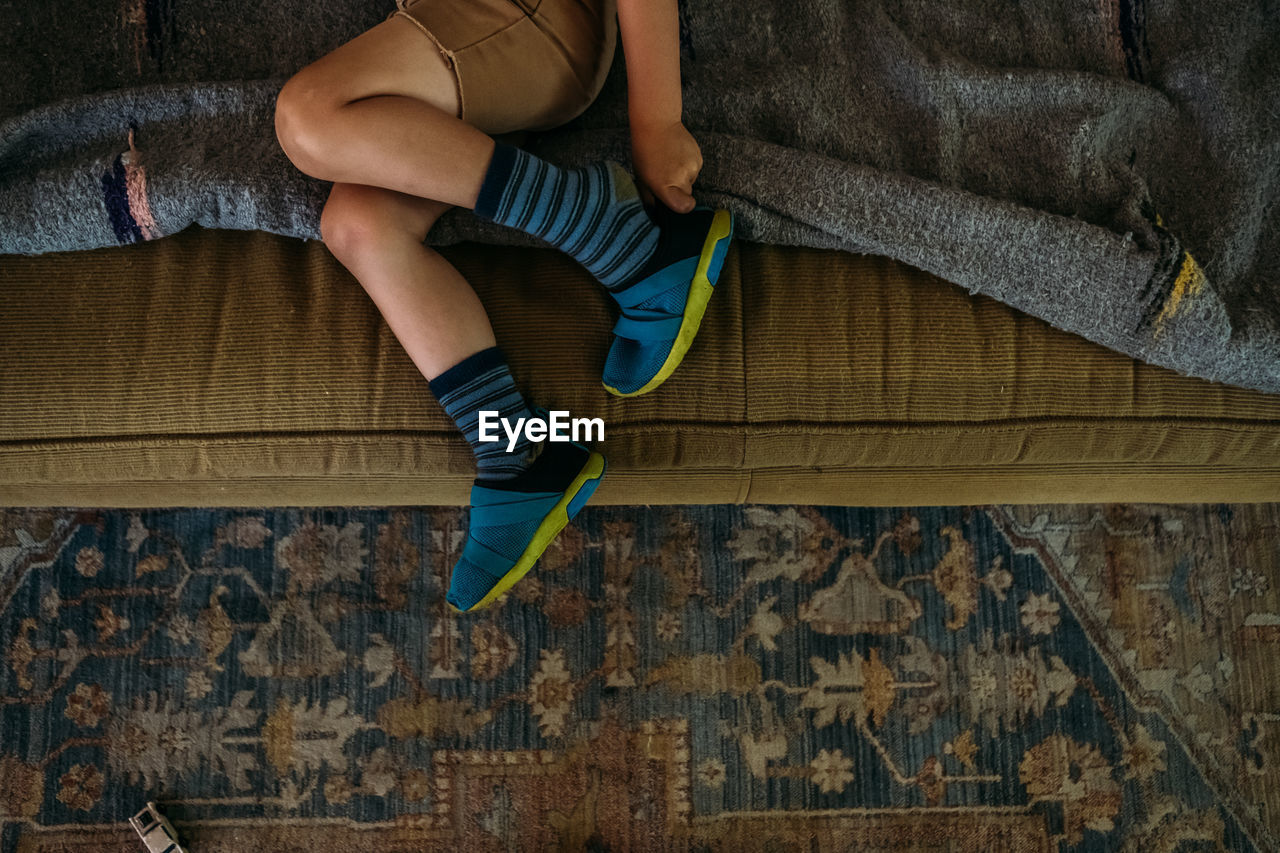 LOW SECTION OF BOY SITTING ON SOFA
