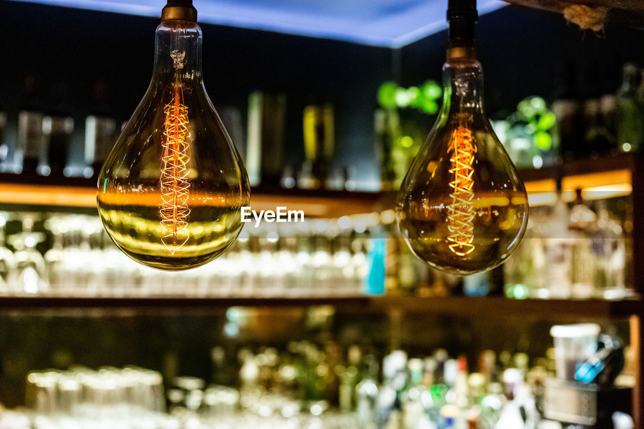 focus on foreground, glass - material, bottle, illuminated, indoors, container, close-up, no people, hanging, transparent, bar - drink establishment, decoration, glass, reflection, food and drink, bar counter, refreshment, still life, restaurant, drink, nightlife